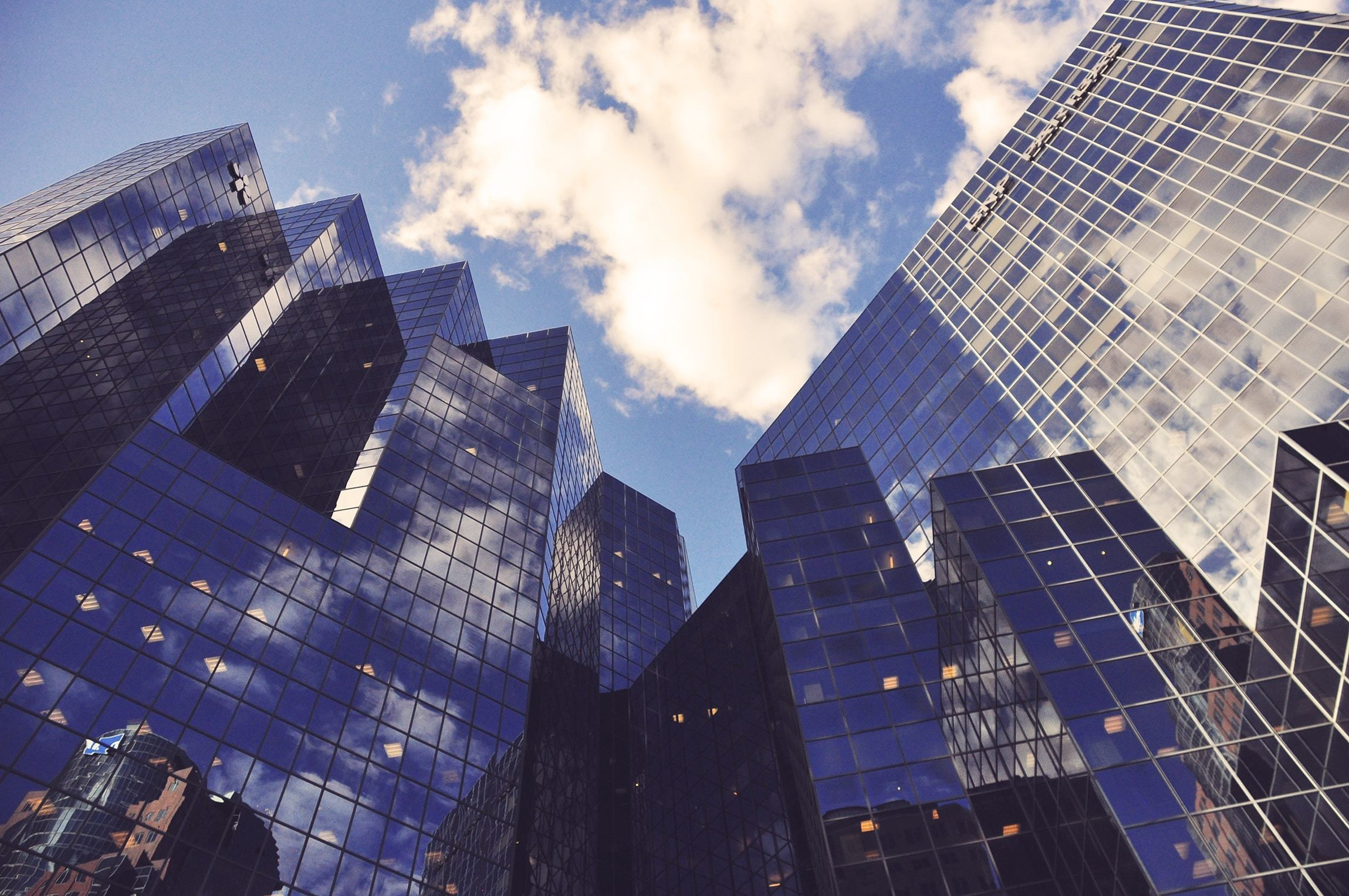 looking up from street level at the reflective windows of skyscrapers