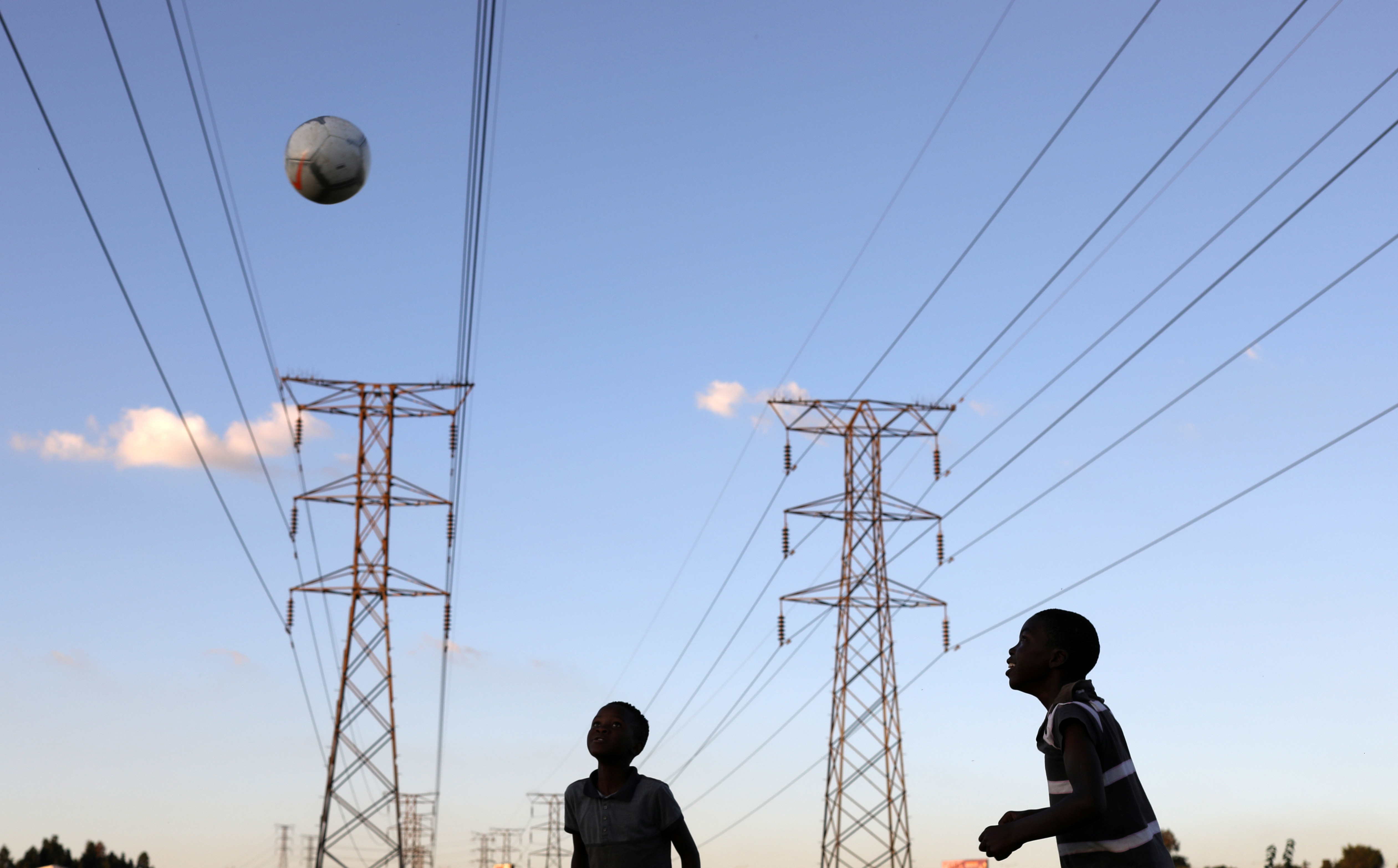 Boys play soccer below electricity pylons in Soweto, South Africa.