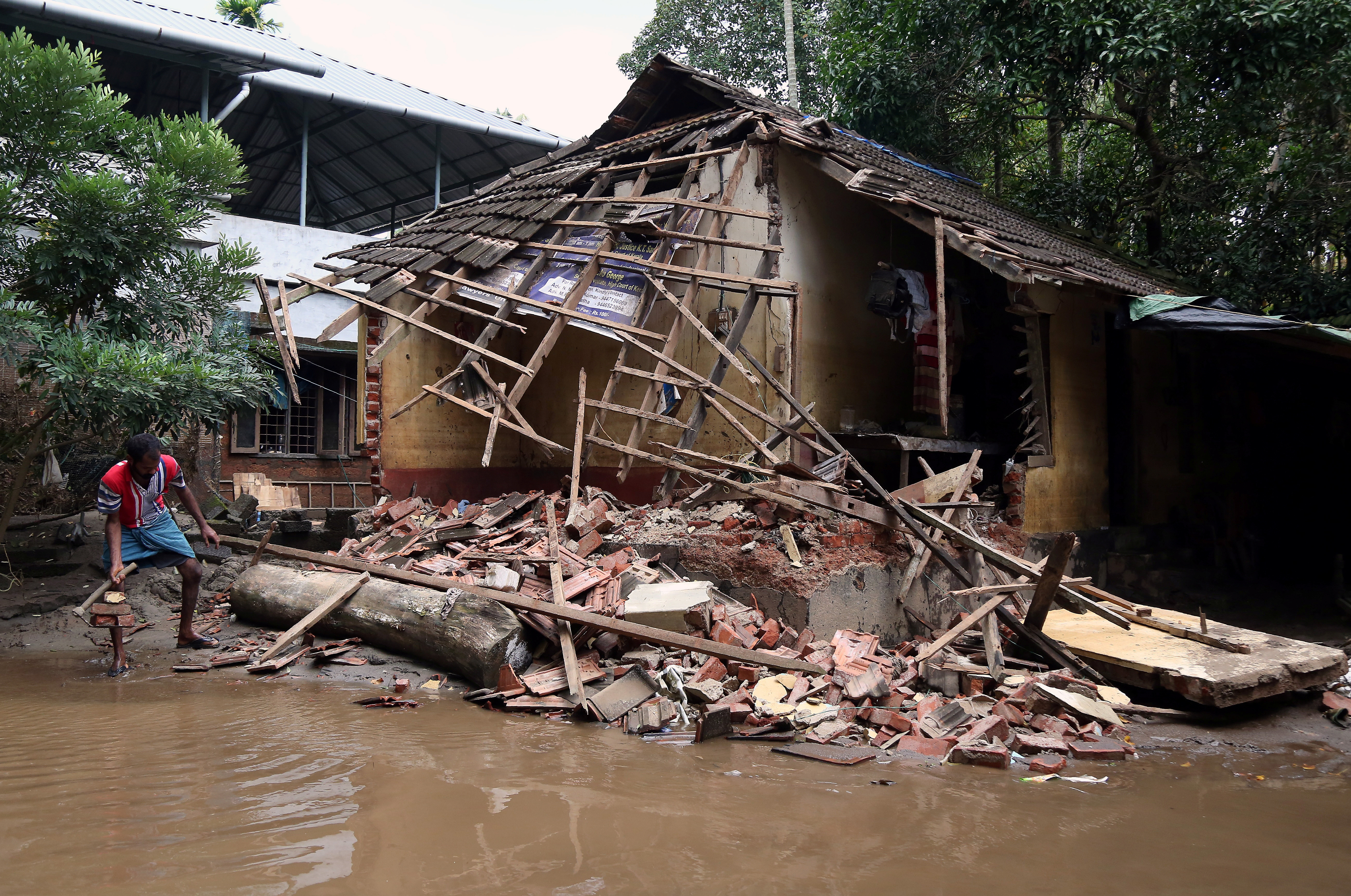 A man removes debris from a collapsed house after the August 2018 floods in Kerala.