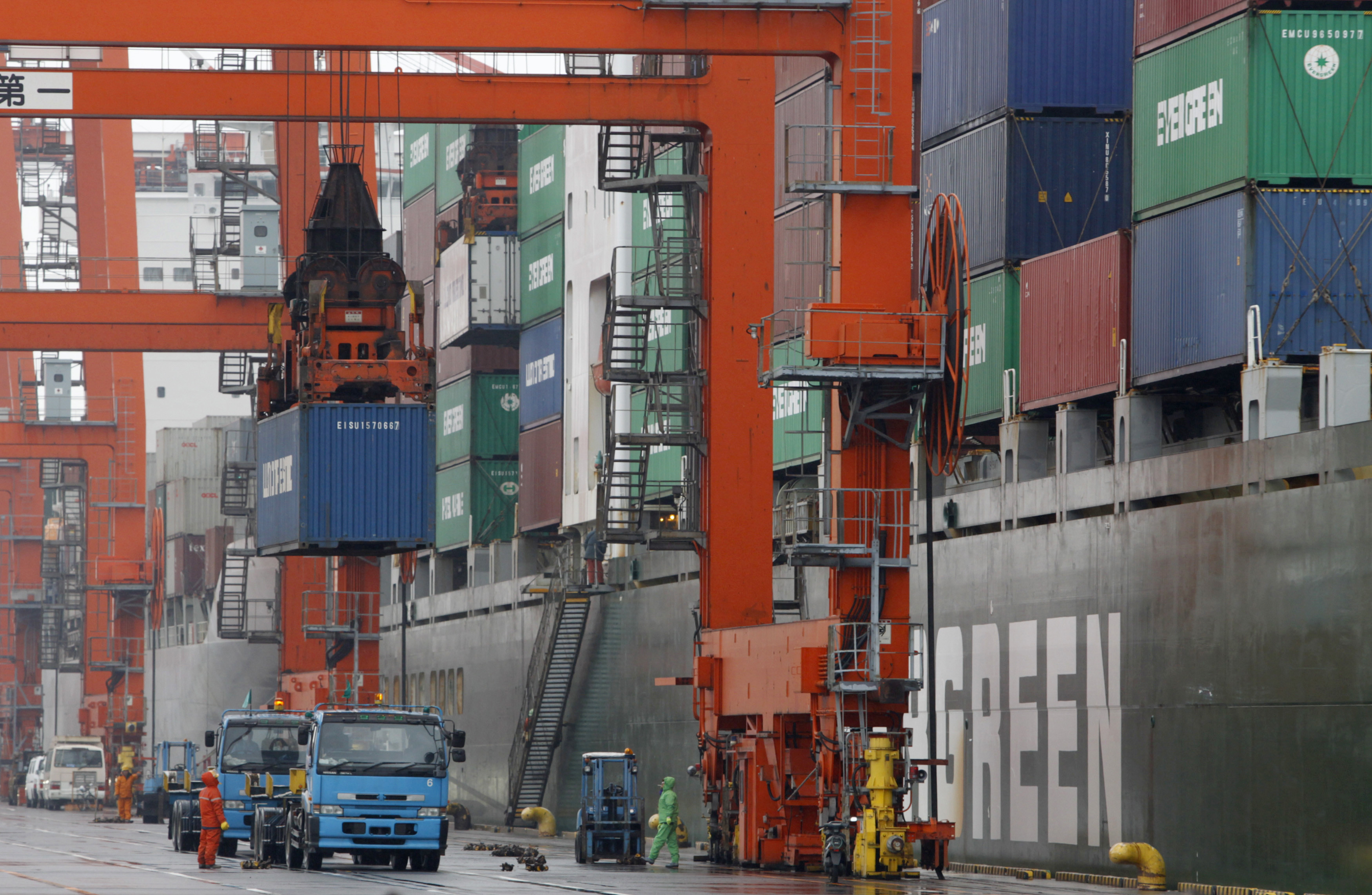 Workers load a cargo container on a truck at a pier in Tokyo March 24, 2010. Japan's exports fell in February from the previous month in a sign that a rebound in external demand could start to slow as the impact of subsidies and stimulus measures wane. REUTERS/Issei Kato (JAPAN - Tags: BUSINESS) - RTR2BZYB