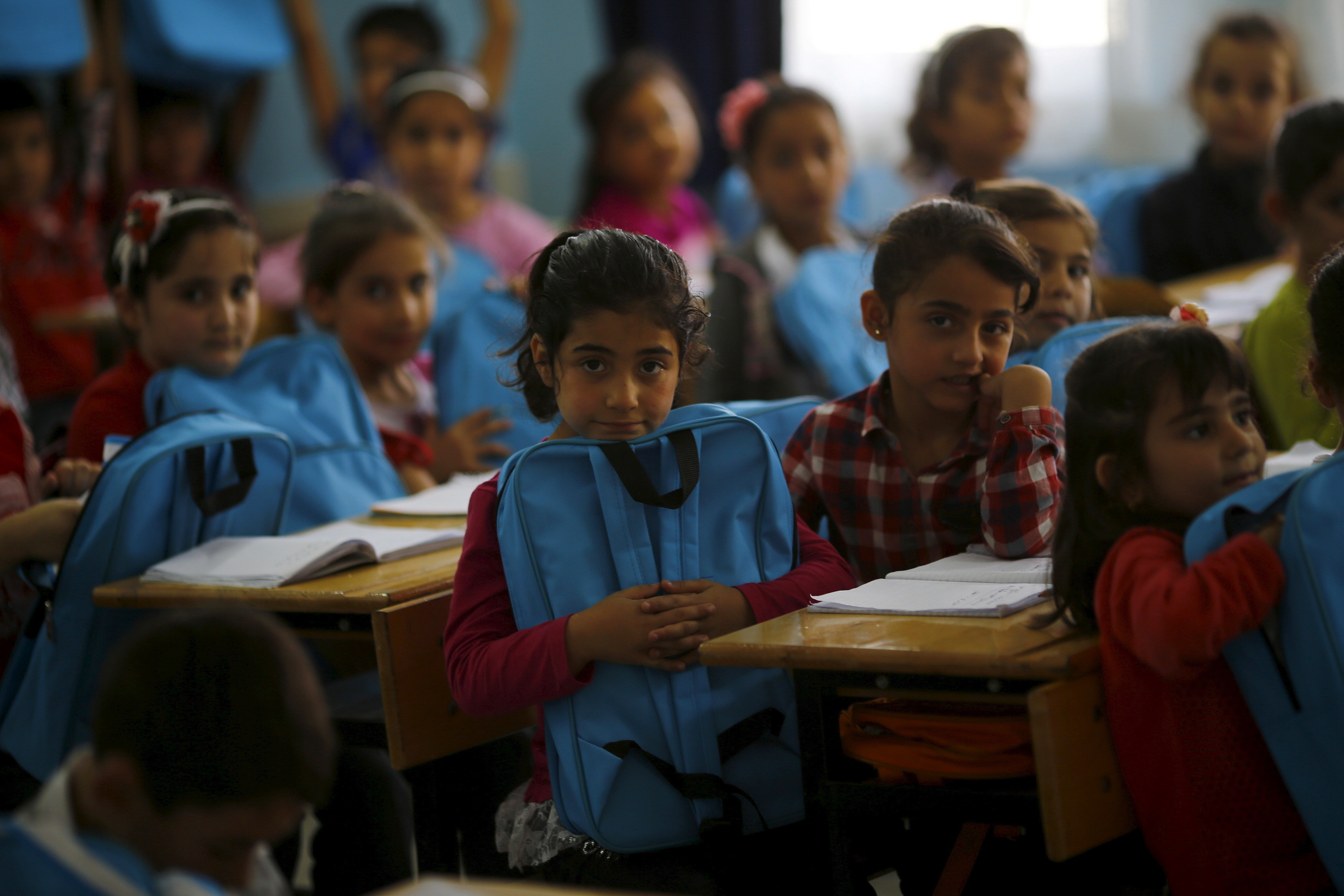 Syrian refugee children are seen during a lesson at Fatih Sultan Mehmet School in Karapurcek district of Ankara, Turkey, October 2, 2015. Out of 640,000 Syrian children in Turkey, 400,000 are not at school, a Turkish official told Reuters on Friday, warning that those who miss out are likely to be exploited by
