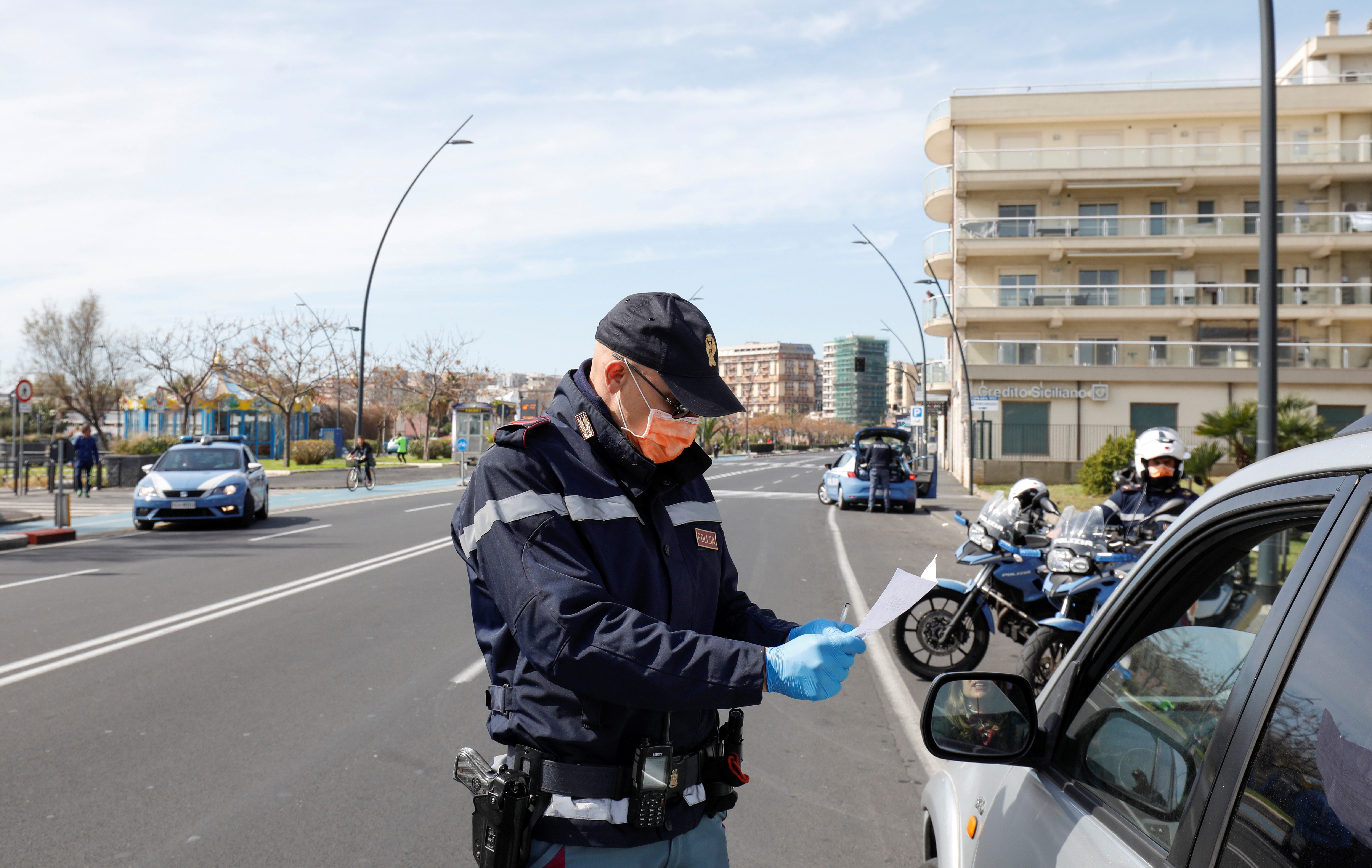 A police officer wearing a protective face mask controls travel documents allowing to leave a home, as the Italian government continues restrictive movement measures to combat the coronavirus outbreak, in Catania, Italy March 14, 2020. REUTERS/Antonio Parrinello - RC2MJF9OSB99