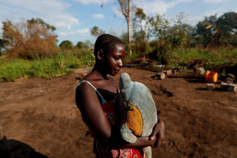 Maria Jofresse, 25, holds a stuffed toy she received for her seventh birthday as she stands where her house stood, in the aftermath of Cyclone Idai, outside the village of Cheia, which means