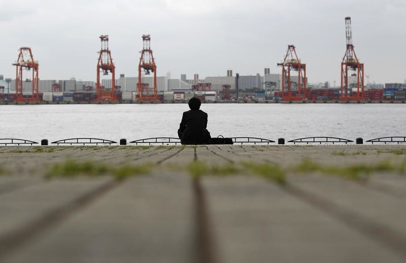 A businessman sits near a cargo area at a port in Tokyo April 19, 2012. Japan's exports rose in March from a year earlier for the first time in six months, mainly on the strength of U.S. sales, but high fuel imports pushed the trade balance back into deficit and manufacturers remain cautious about business in months ahead. REUTERS/Toru Hanai (JAPAN - Tags: BUSINESS) - RTR30XD8