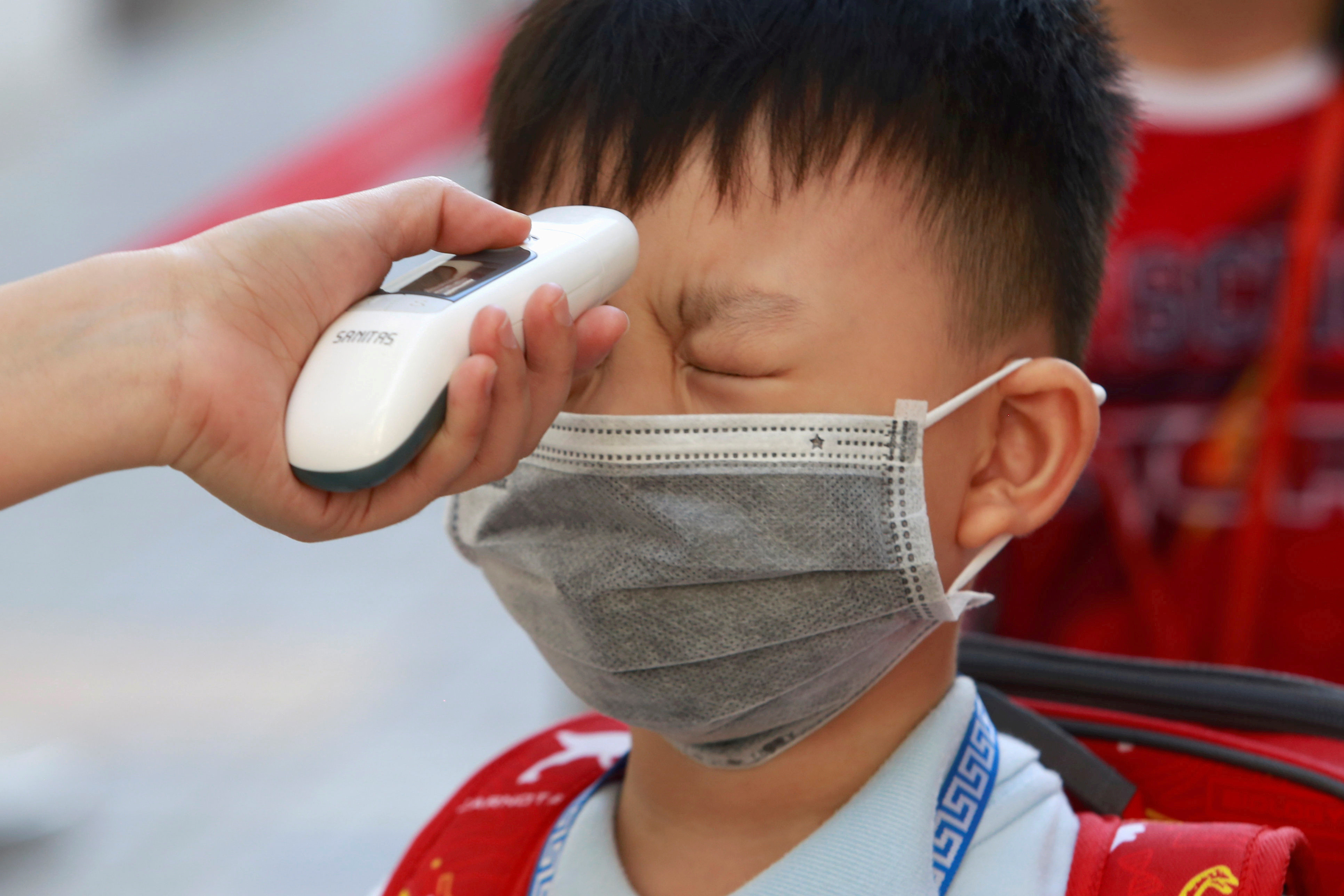A primary school student undergoes a temperature check on the first day of class after the government eased a nationwide lockdown during the coronavirus disease (COVID-19) outbreak in Ho Chi Minh, Vietnam May 11, 2020. REUTERS/Yen Duong     TPX IMAGES OF THE DAY - RC23MG9G60XF