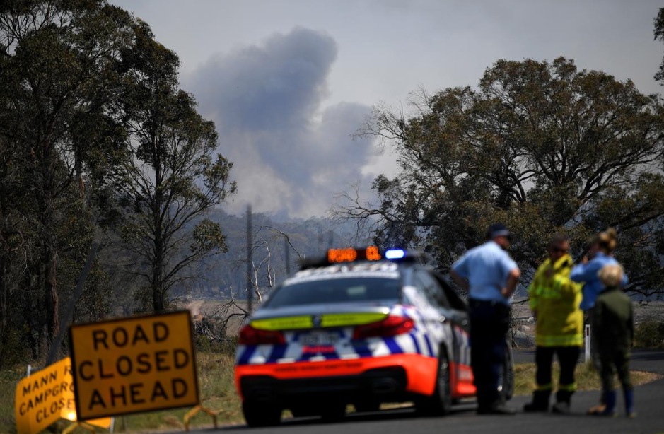 Smoke from a large bushfire is seen from a roadblock outside Wytaliba, near Glen Innes, Australia.