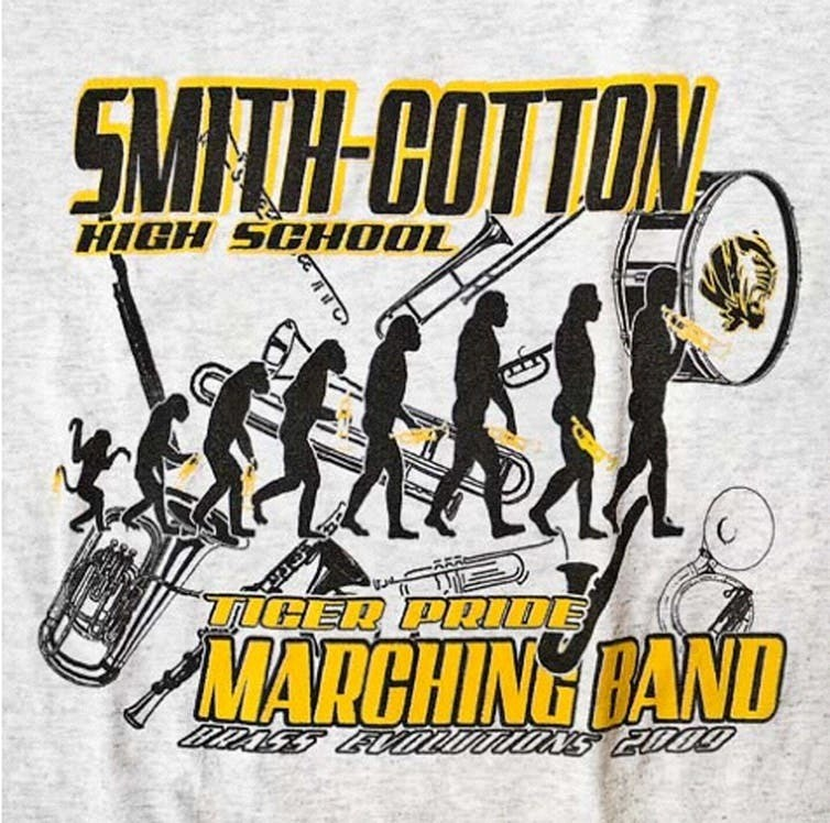 A high school marching band's T-shirt places a horn-playing Homo sapiens at the end of the evolutionary process.
