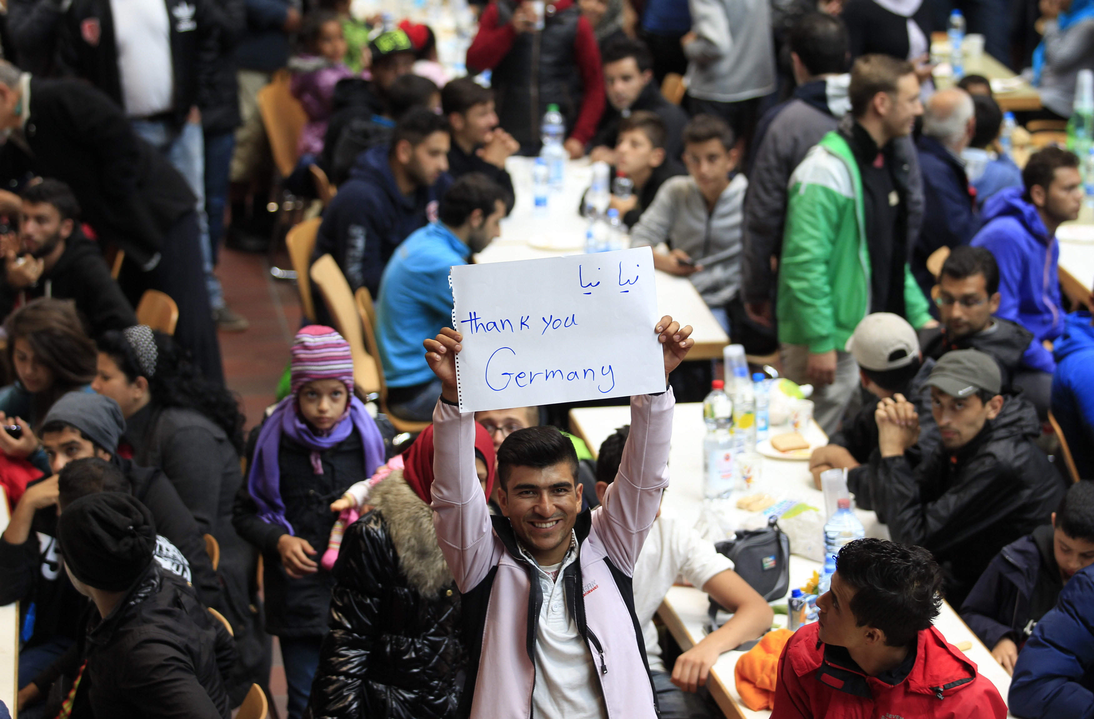 A migrant holds up a placard at a registration centre after arriving at the main railway station in Dortmund, Germany September 6, 2015. Austria and Germany threw open their borders to thousands of exhausted migrants on Saturday, bussed to the Hungarian border by a right-wing government that had tried to stop them but was overwhelmed by the sheer numbers reaching Europe's frontiers.  REUTERS/Ina Fassbender - RTX1RB6Z