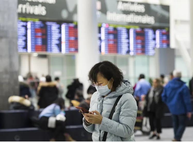 A woman wears a mask in the arrivals section of the international terminal at Toronto Pearson International Airport.