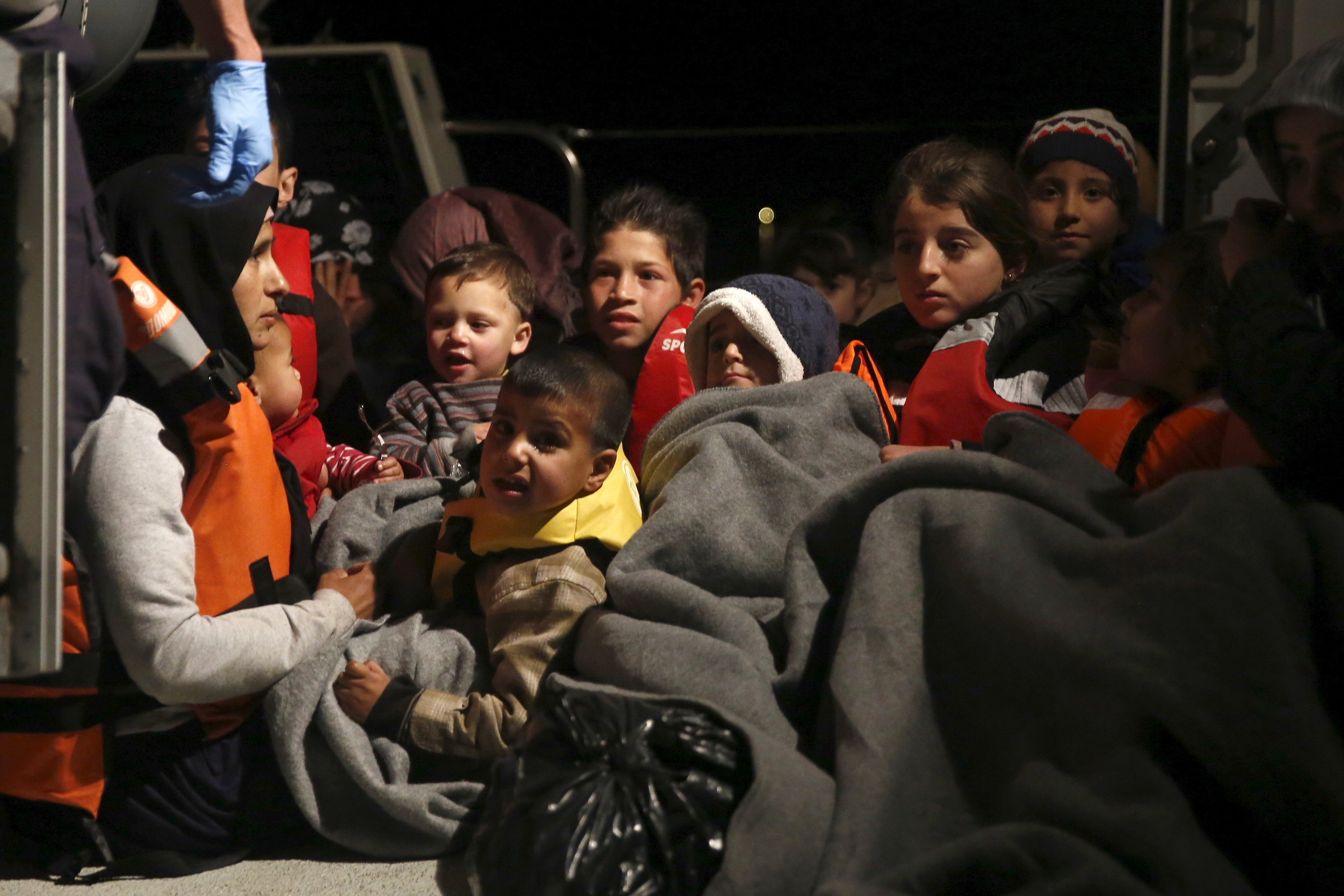 Refugee children are seen onboard a Greek Coast Guard vessel, carrying other refugees and migrants, as it arrives at the port of Mytilene on the Greek island of Lesbos, following a rescue operation at open sea, April 5, 2016. REUTERS/Giorgos Moutafis - RTSDMDU