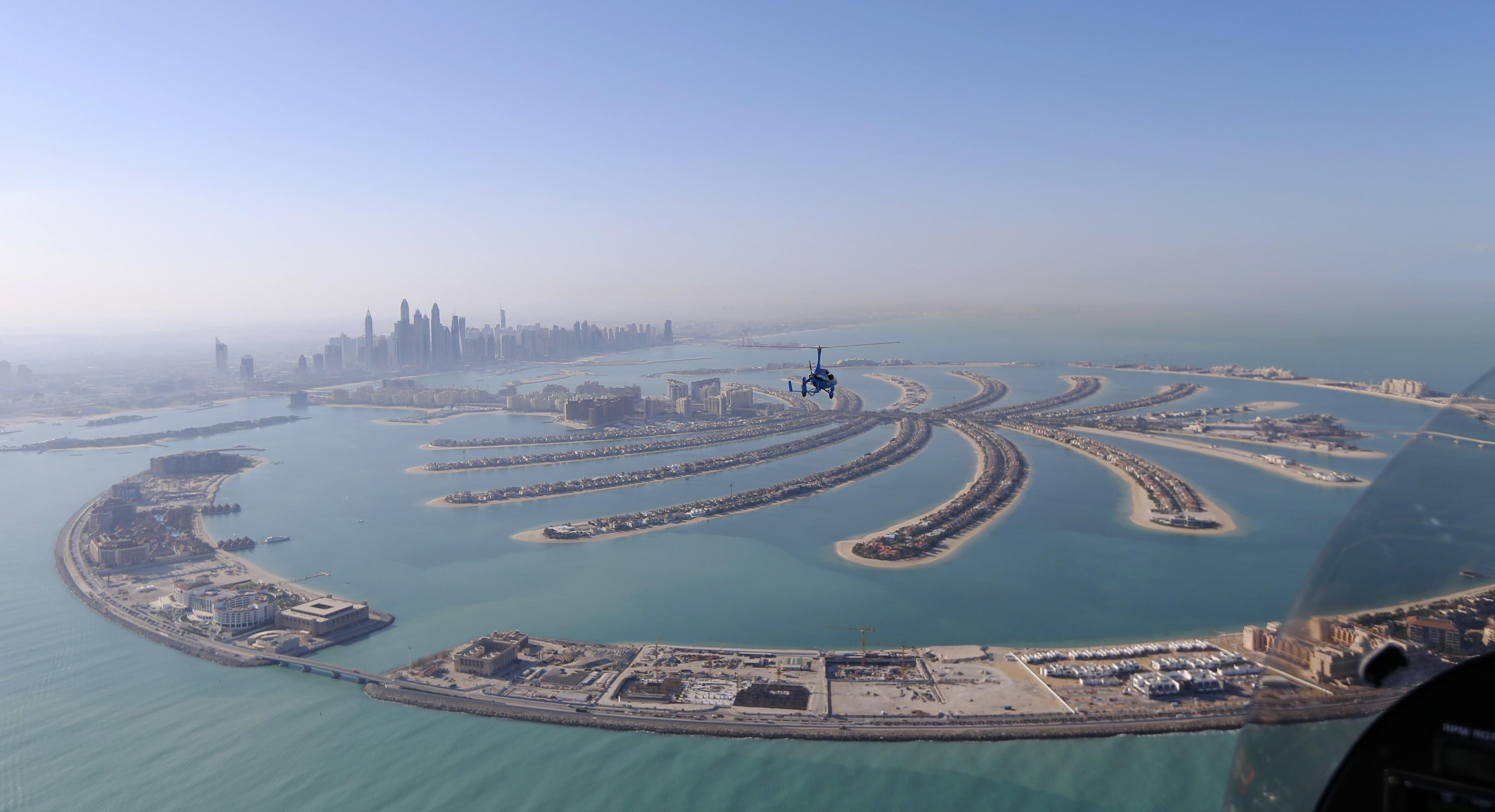 A helicopter flies over the Jumeirah neighbourhood in Dubai, UAE December 9, 2015.