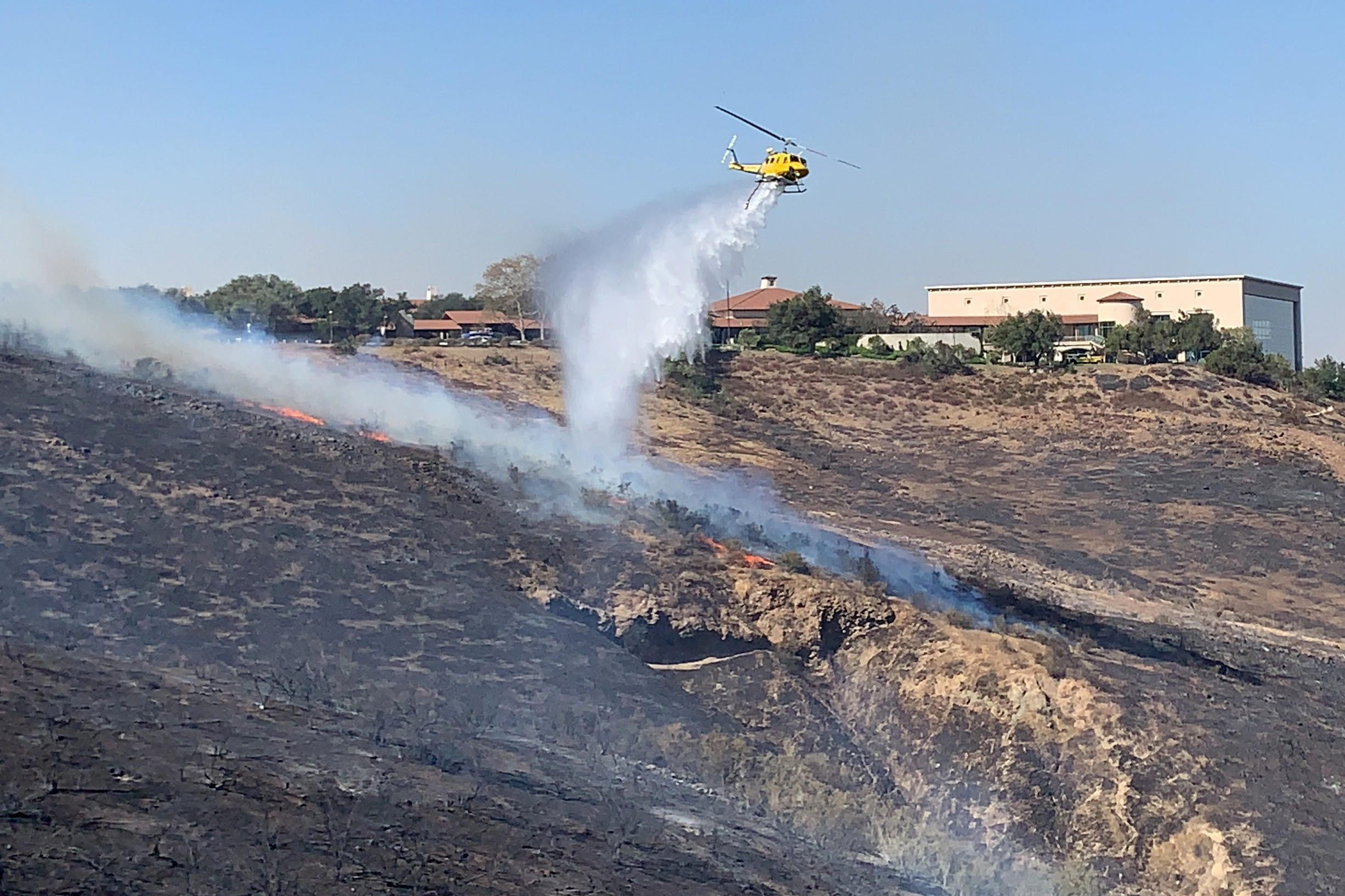 A helicopter drops water on a fire burning on a hillside near the Reagan Presidential library.