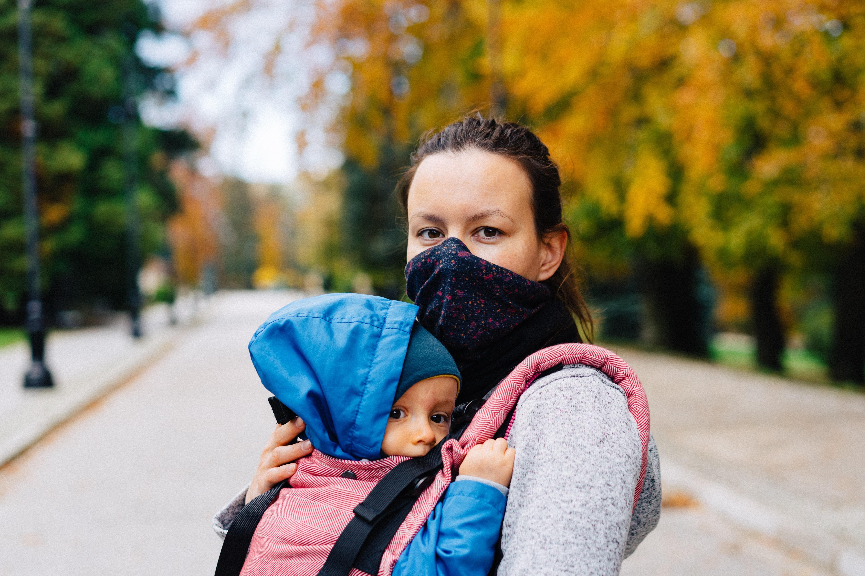 Masked mother holding child