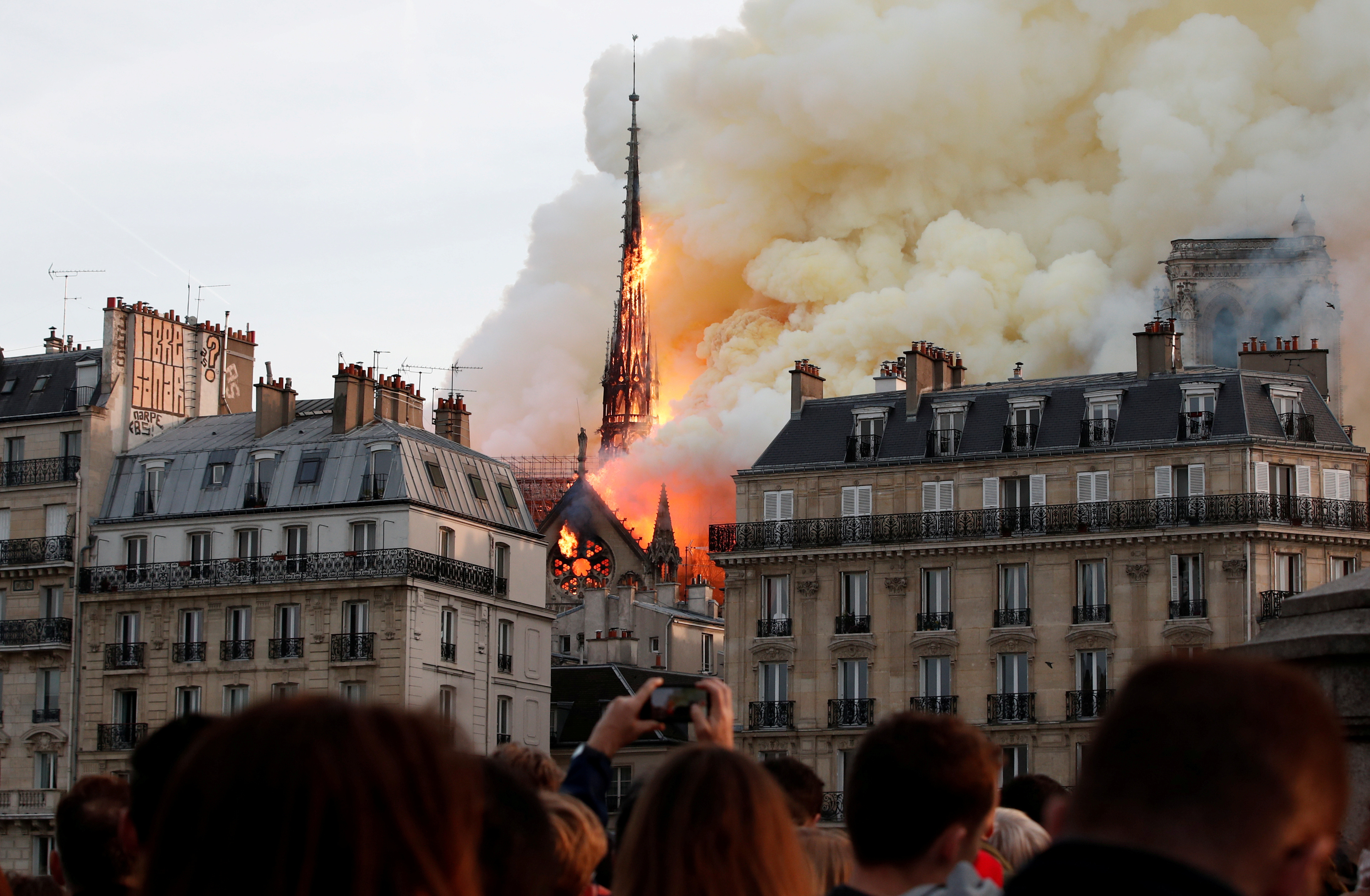 Smoke billows as fire engulfs the spire of Notre Dame Cathedral in Paris, France, April 15, 2019. Picture taken April 15, 2019