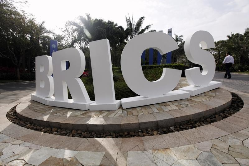 A man walks past a signage decoration for the BRICS summit outside Sheraton Hotel, the venue for the third BRICS summit in Sanya, Hainan province April 14, 2011.