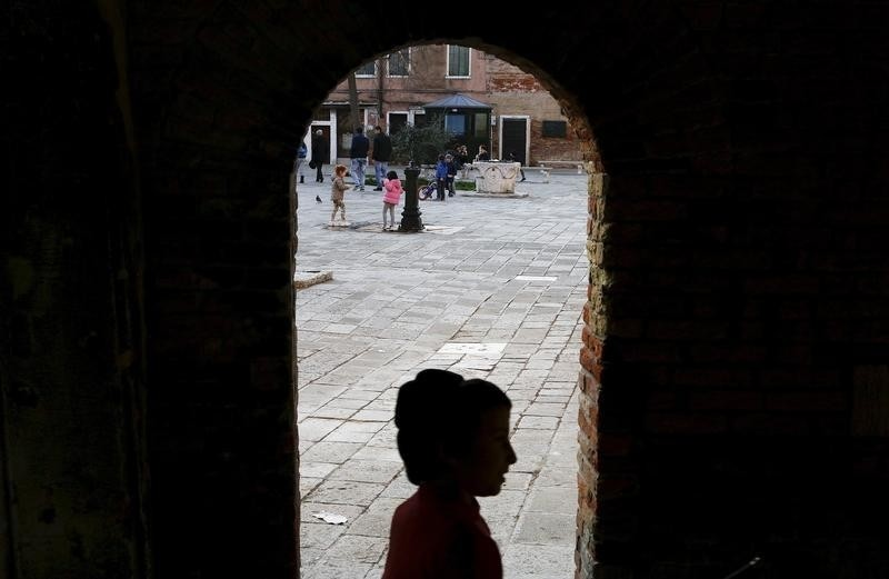 A boy stands in an archway in Venice.