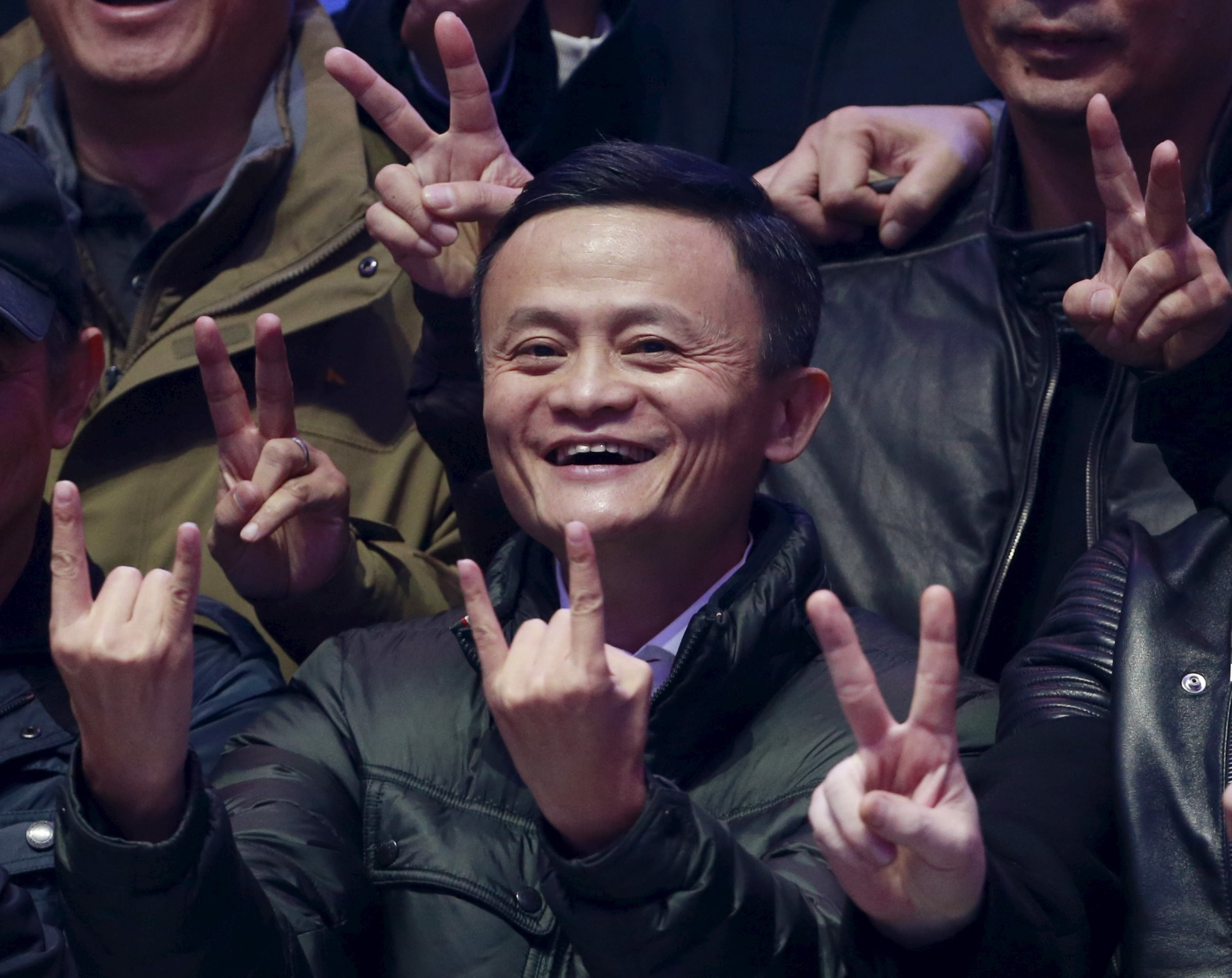 Alibaba founder and chairman Jack Ma smiles as he poses with attendants after watching real-time data of transactions at Alibaba Group's 11.11 Global shopping festival in Beijing, China.