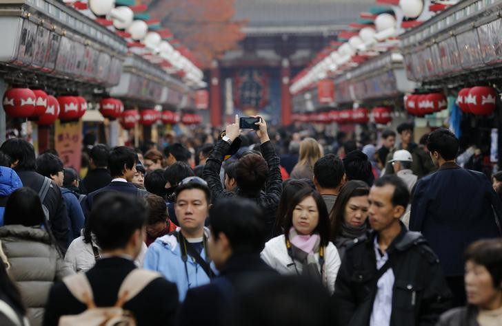 A visitor takes pictures of Nakamise shopping street on Asakusa district in Tokyo November 28, 2014. Tokyo is a place of pulsing clubs, steep-roofed temples, narrow lanes packed with smoky restaurants where meat sizzles on grills and karaoke pubs whose yowled anthems spill into the streets. REUTERS/Yuya Shino (JAPAN - Tags: TRAVEL)