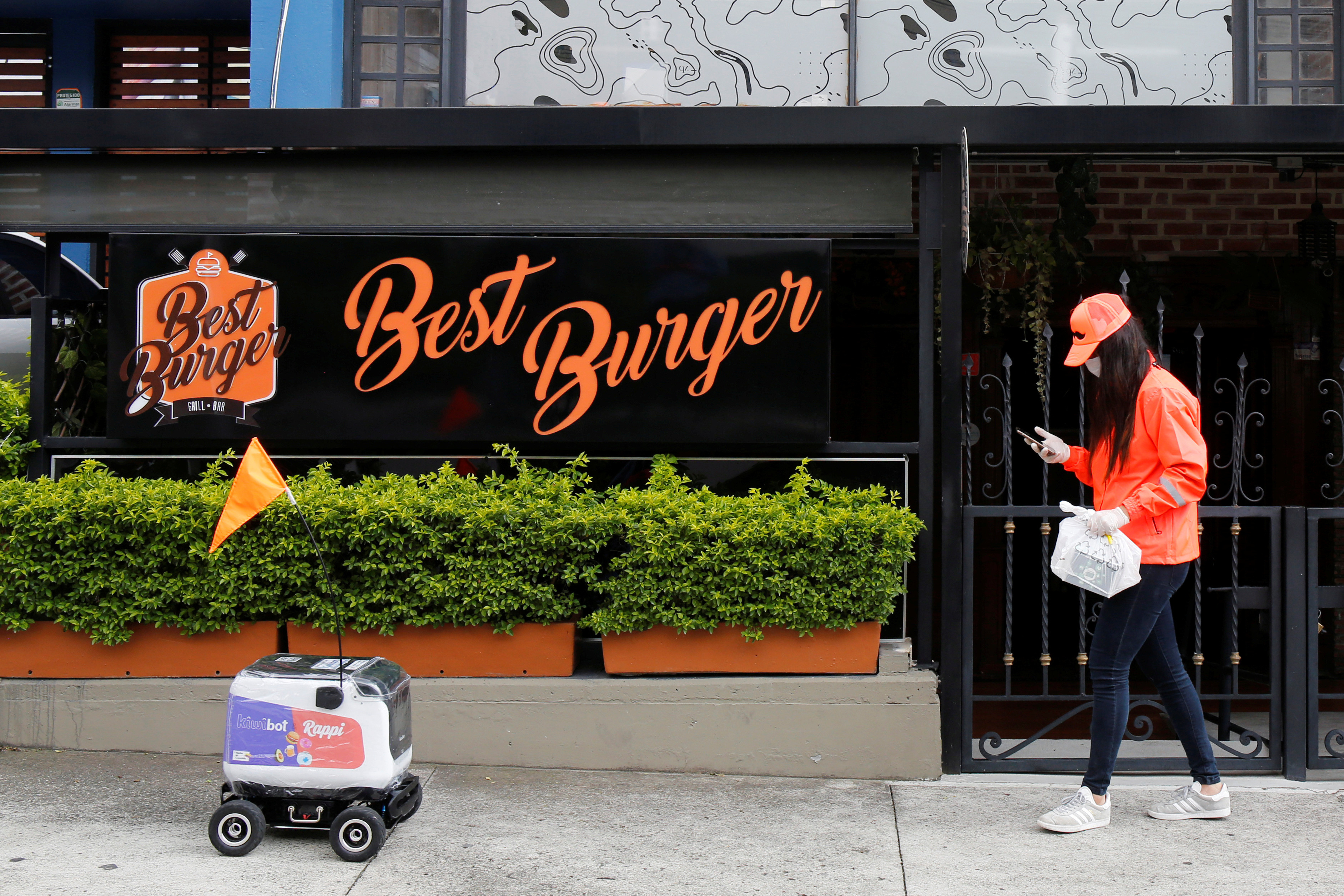 Rappi delivery woman wearing a face mask walks in front of a delivery robot from the Colombian company Rappi amid the coronavirus disease (COVID-19) outbreak in Medellin, Colombia April 17, 2020. REUTERS/David Estrada - RC2L6G975RNZ