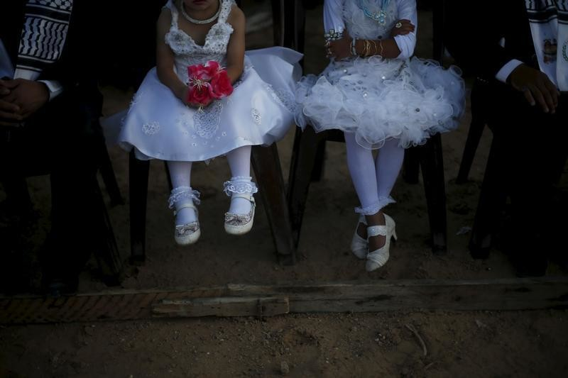 Girls accompany grooms as they sit separate from the brides during a mass wedding for 150 couples in Beit Lahiya town in the northern Gaza Strip July 20, 2015.