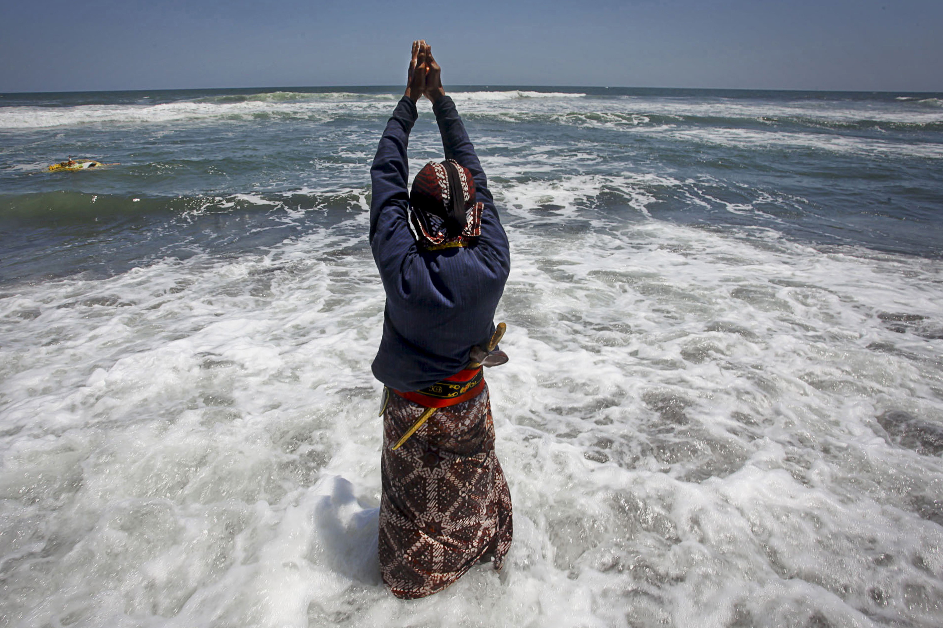 A Javanese man from Yogyakarta Palace pray at Goa Cemara beach during a ceremony ahead of the Javanese New Year in Bantul, near the ancient city of Yogyakarta,