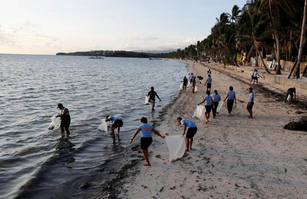 Policemen collect trash at Bulabog beach in the holiday island of Boracay during the first day of a temporary closure for tourists, in Philippines April 26, 2018.
