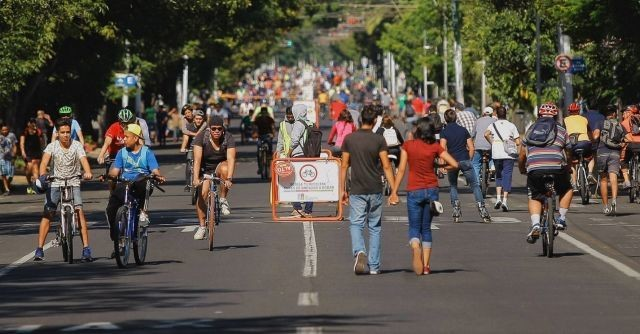 Cyclists and pedestrians in the street on a Sunday in Guadalajara.