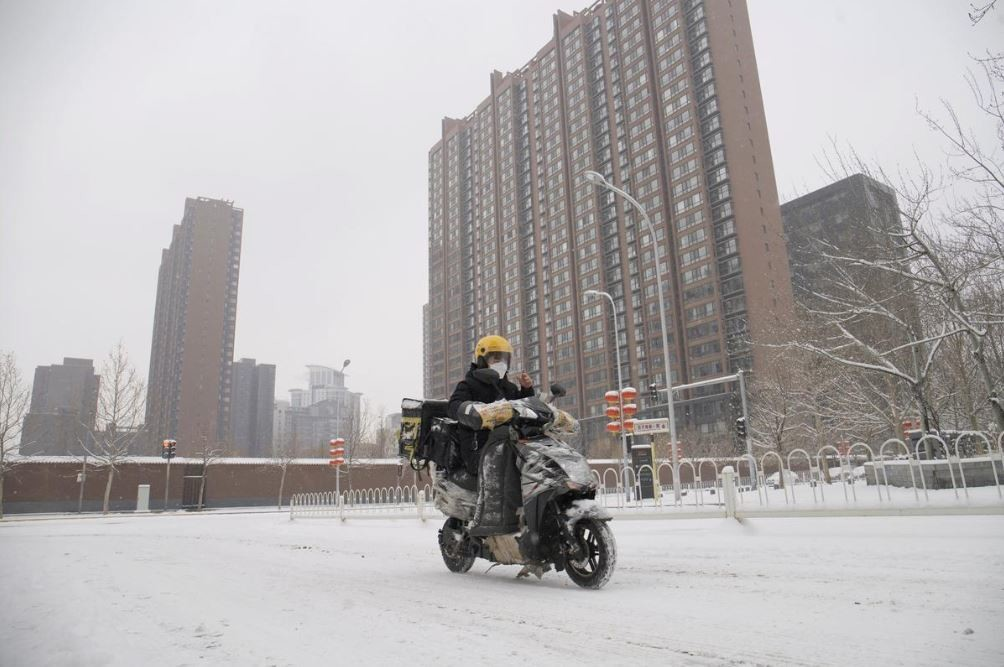 A food delivery worker rides his bike amid snow at a residential compound, as the country is hit by an outbreak of the novel coronavirus, in Beijing, China February 6, 2020.