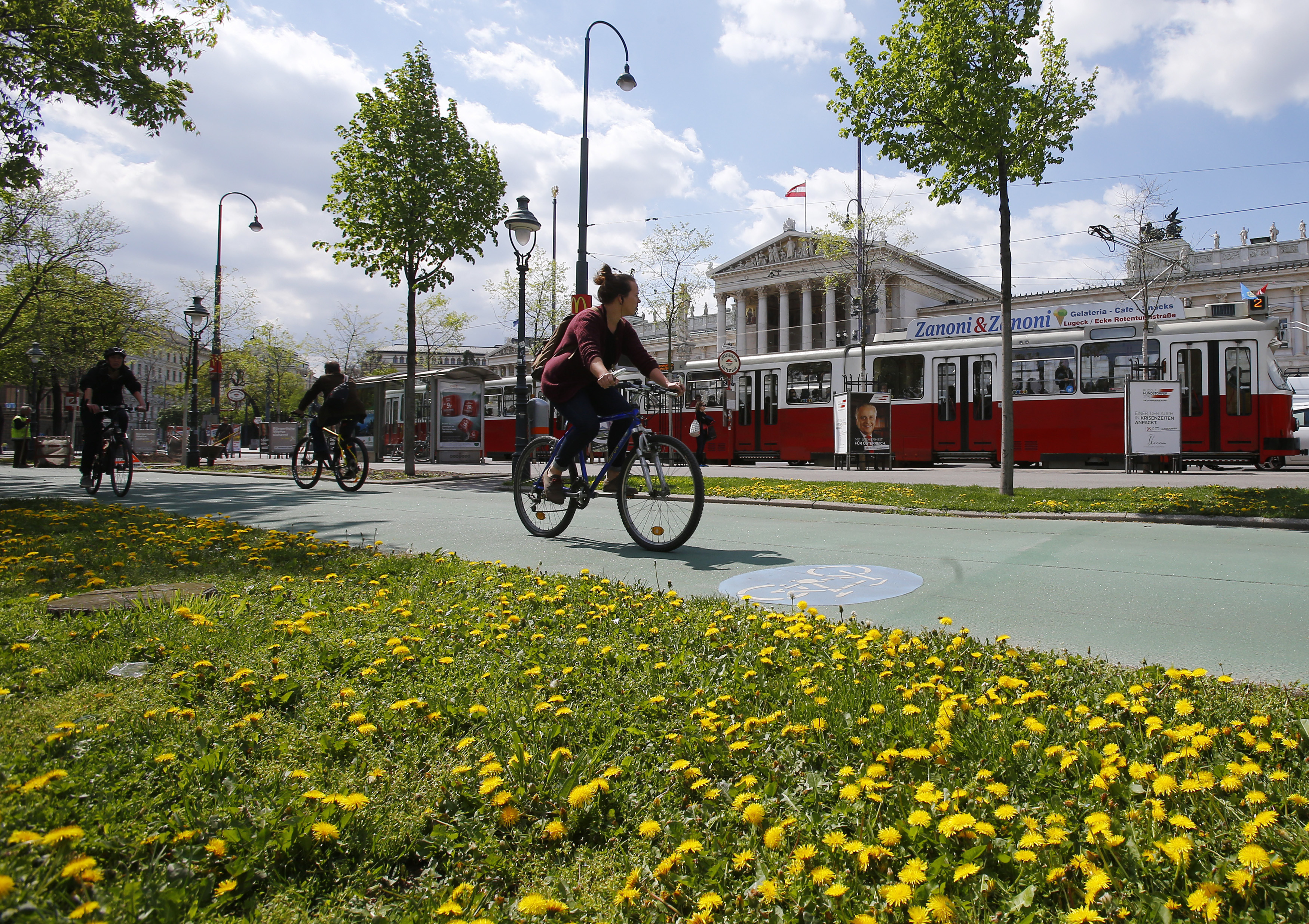Cyclists ride their bikes along Ringstrasse boulevard in front of the parliament in Vienna, Austria, April 19, 2016.