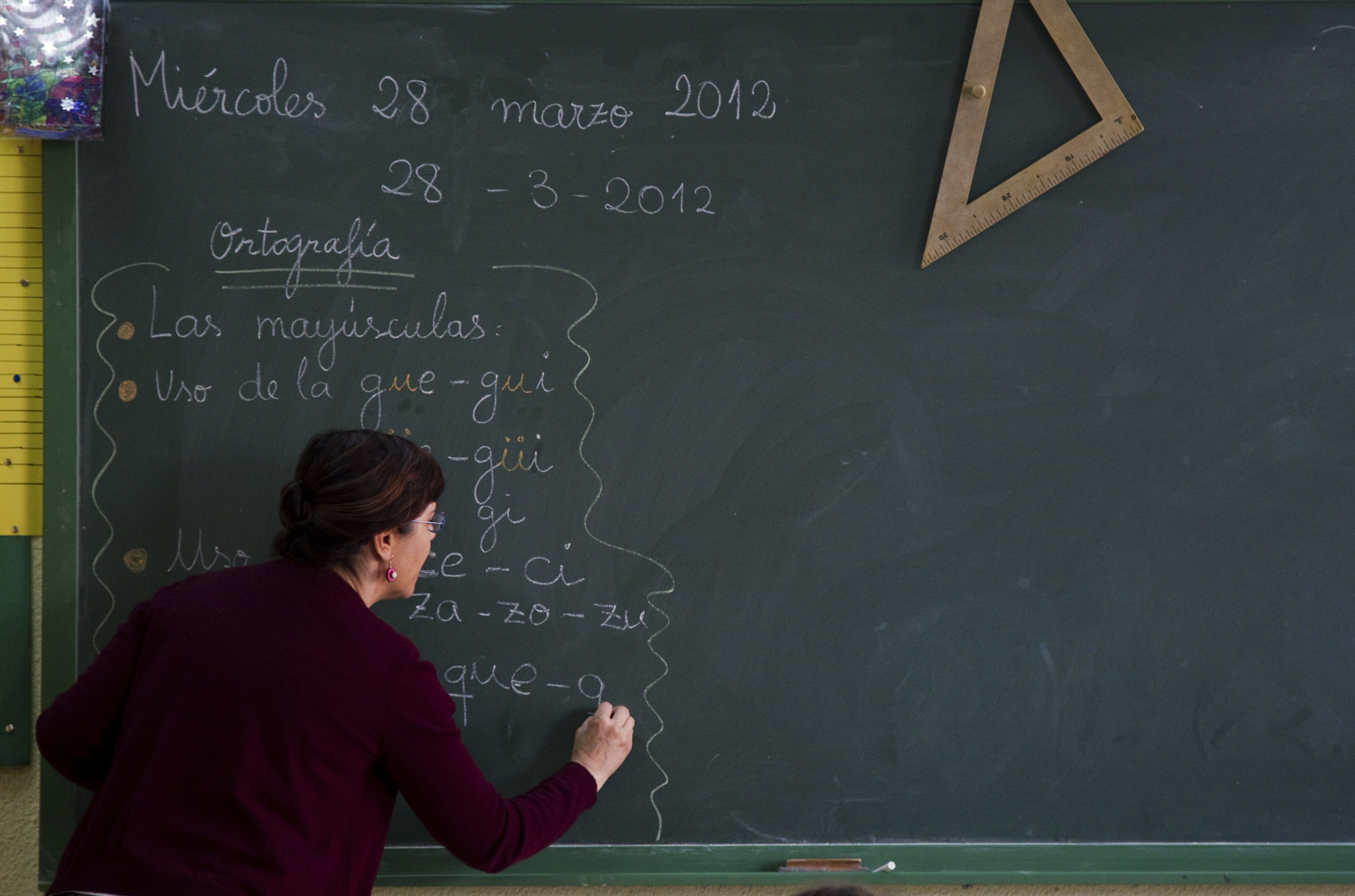 A teacher writes on a blackboard during class at a public school in Madrid, March 28, 2012. Spain will announce some of its deepest budget cuts ever on Friday, though evaporating growth prospects mean it is likely to fall short of what is needed to meet strict public deficit targets. Cuts in public education have sparked nationwide protests and more cuts are likely to be handed down by autonomous regions after the newly installed conservative central government presents its 2012 budget on Friday. REUTERS/Sergio Perez (SPAIN - Tags: EDUCATION BUSINESS SOCIETY POLITICS) - RTR3005W