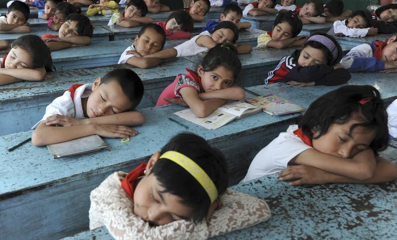An ethnic minority student looks up as her classmates take naps on the desks during their lunch break at a primary school in Akqi county of Kizilsu Kirgiz Autonomous Prefecture, Xinjiang Uighur Autonomous Region June 5, 2012. REUTERS/Stringer (CHINA - Tags: SOCIETY EDUCATION) CHINA OUT. NO COMMERCIAL OR EDITORIAL SALES IN CHINA - GM1E8651K0Y01