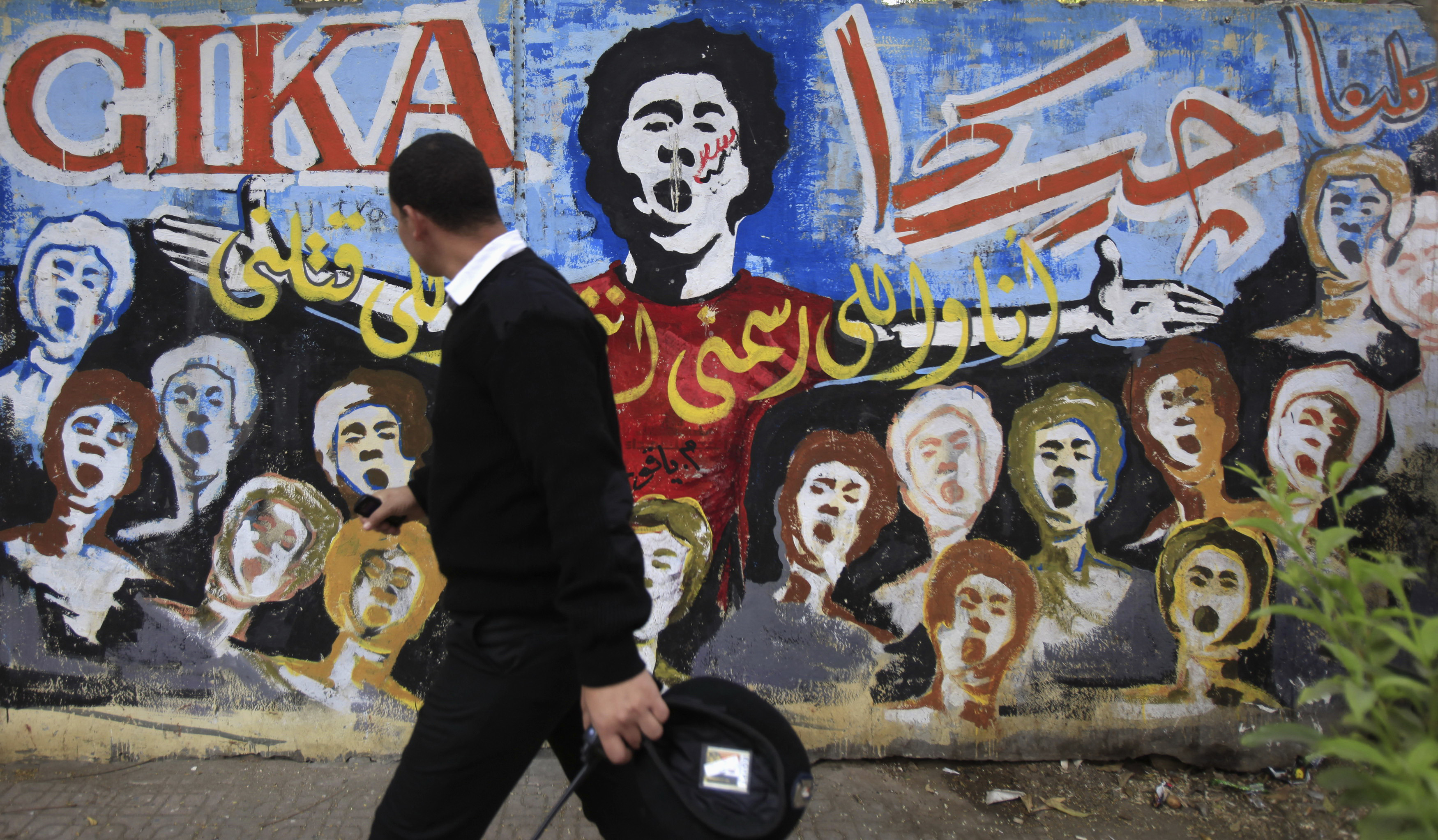 An Egyptian police officer passes a mural depicting youth activist killed during the 2011 Cairo uprising, which was organized through social media.