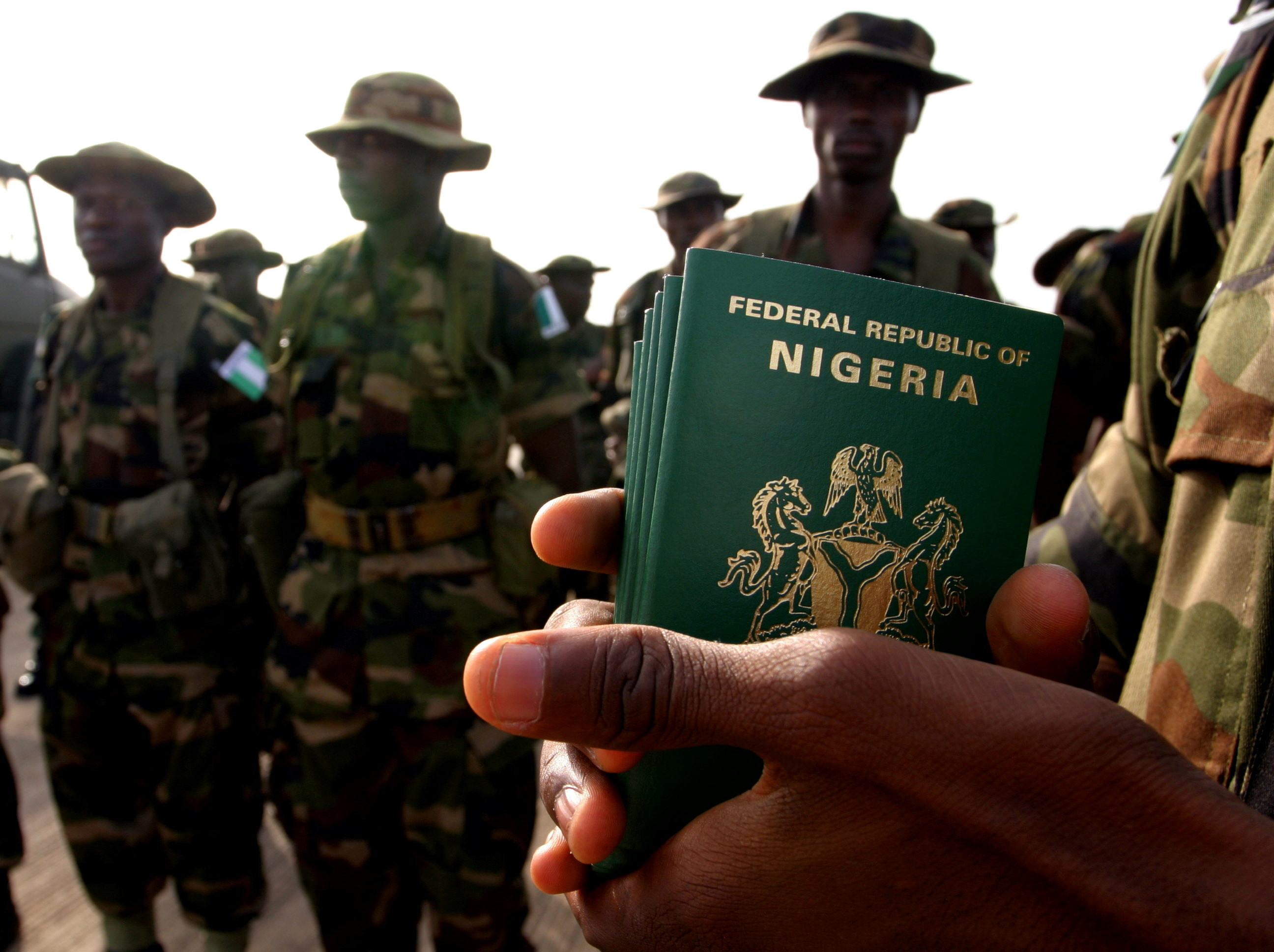 A Nigerian officer holds passports for his troops preparing to board a U.S. military plane in the Nigerian capital Abuja October 28, 2004, before flying to El-Fasher in Darfur to reinforce an expanded African Union peacekeeping effort in the violent region of western Sudan. The U.S. airlift is the first U.S. military deployment in the Darfur conflict. - RTXN07N