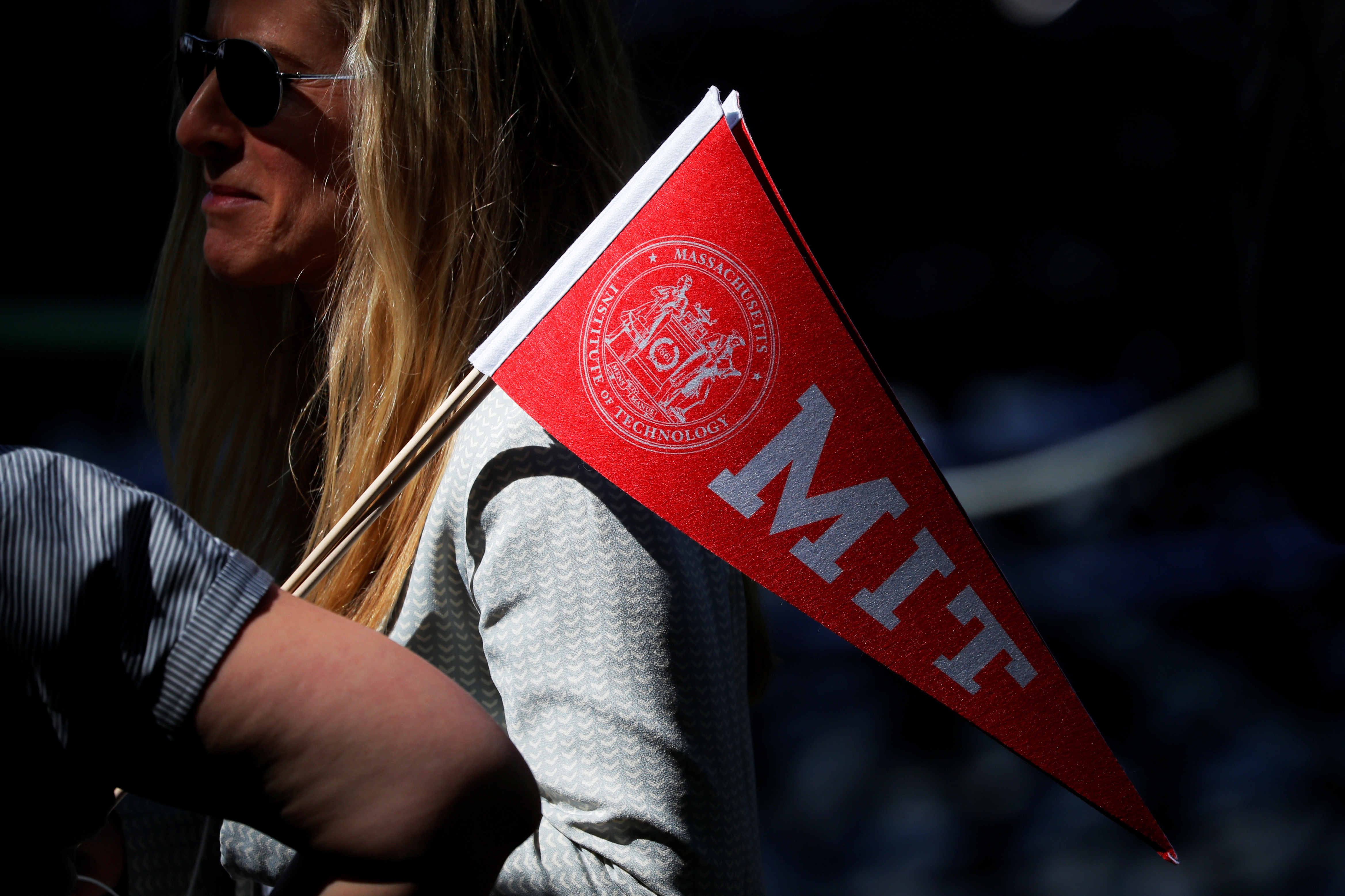 An audience member carries a school pennant before Commencement Exercises at the Massachusetts Institute of Technology (MIT) in Cambridge, Massachusetts, U.S., June 7, 2019. REUTERS/Brian Snyder - RC18F15B8A70