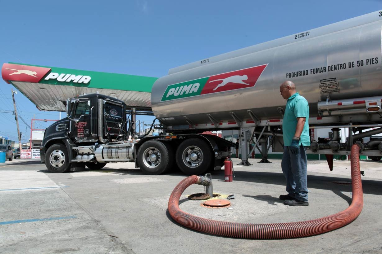 The driver of a gas truck discharges fuel at a gas station, after the island was hit by Hurricane Maria in San Juan, Puerto Rico
