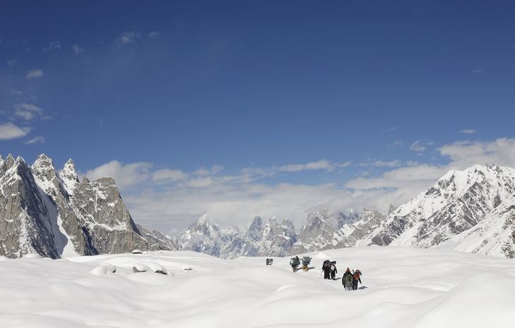 Trekkers and porters hike down the Baltoro glacier in the Karakoram mountain range in Pakistan September 7, 2014. Geographically, Pakistan is a climbers paradise. It rivals Nepal for the number of peaks over 7,000 meters and is home to the world's second tallest mountain, K2, as well as four of the world's 14 summits higher than 8,000 meters. In more peaceful times, northern Pakistan's unspoilt beauty was a major tourist draw but the potentially lucrative industry has been blighted by years of violence. The number of expeditions has dwindled, wrecking communities dependant on climbing for income and starving Pakistan's suffering economy of much-needed dollars. Picture taken September 7, 2014. REUTERS/Wolfgang Rattay    (PAKISTAN - Tags: ENVIRONMENT SOCIETY BUSINESS EMPLOYMENT TPX IMAGES OF THE DAY TRAVEL) ATTENTION EDITORS - PICTURE 31 OF 32 FOR WIDER IMAGE STORY 'K2 - THE SAVAGE MOUNTAIN' SEARCH 'RATTAY K2' FOR ALL IMAGES