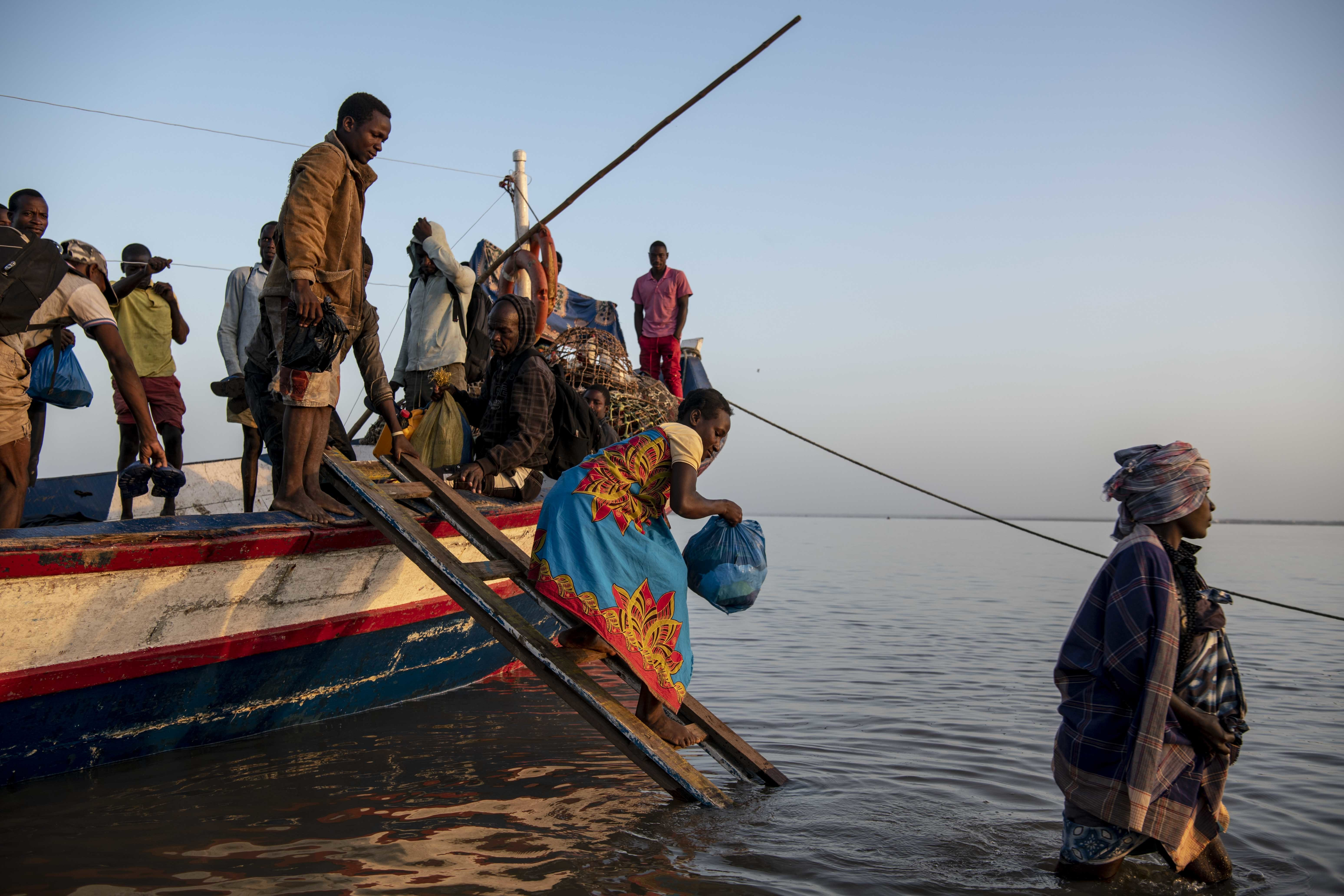 People displaced by Cyclone Idai disembark a boat at dawn on at the port of Beira.