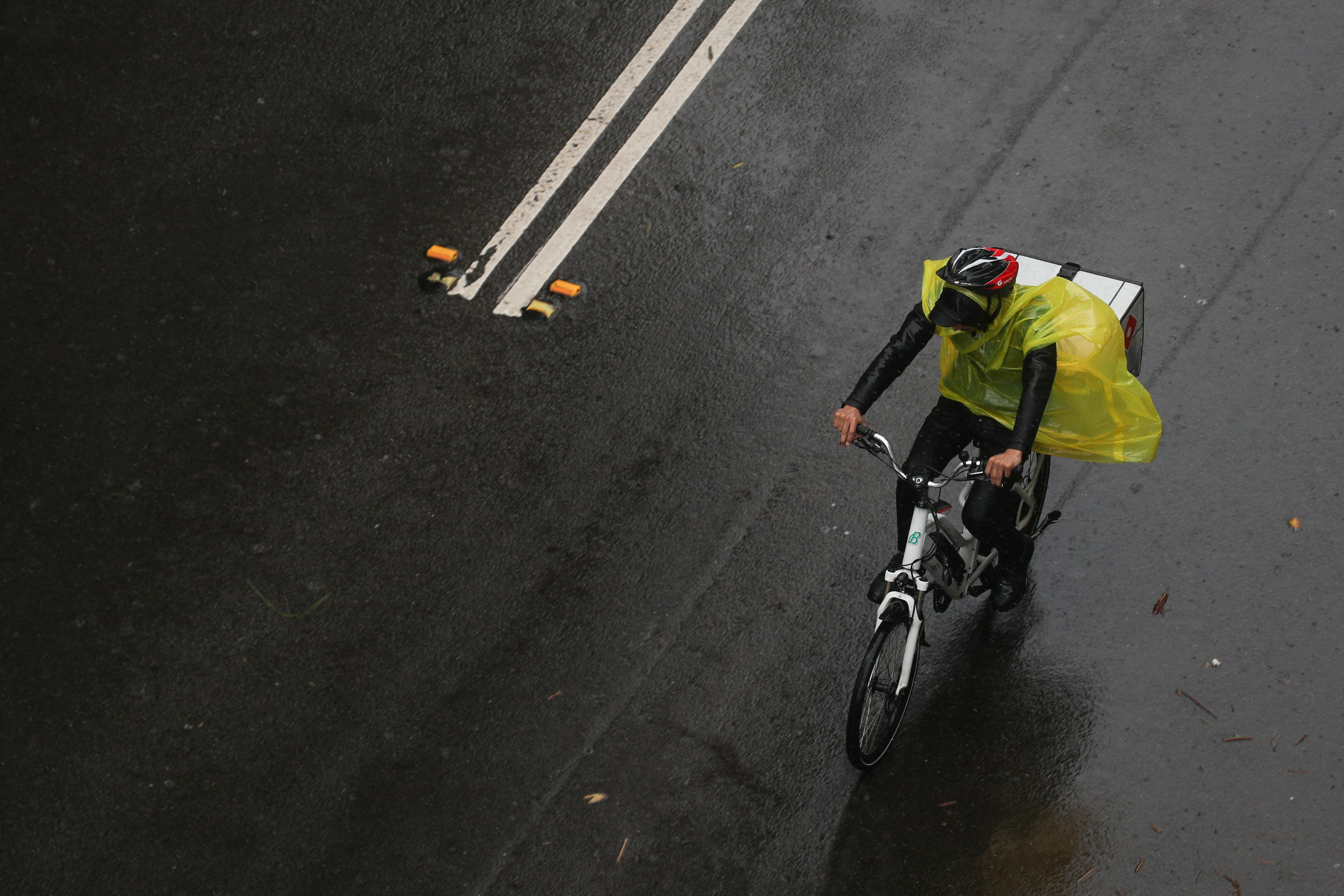 A bicycle deliveryman braves strong wind and rain in Sydney, New South Wales, Australia, February 9, 2020.  REUTERS/Loren Elliott - RC2PWE9OMABW