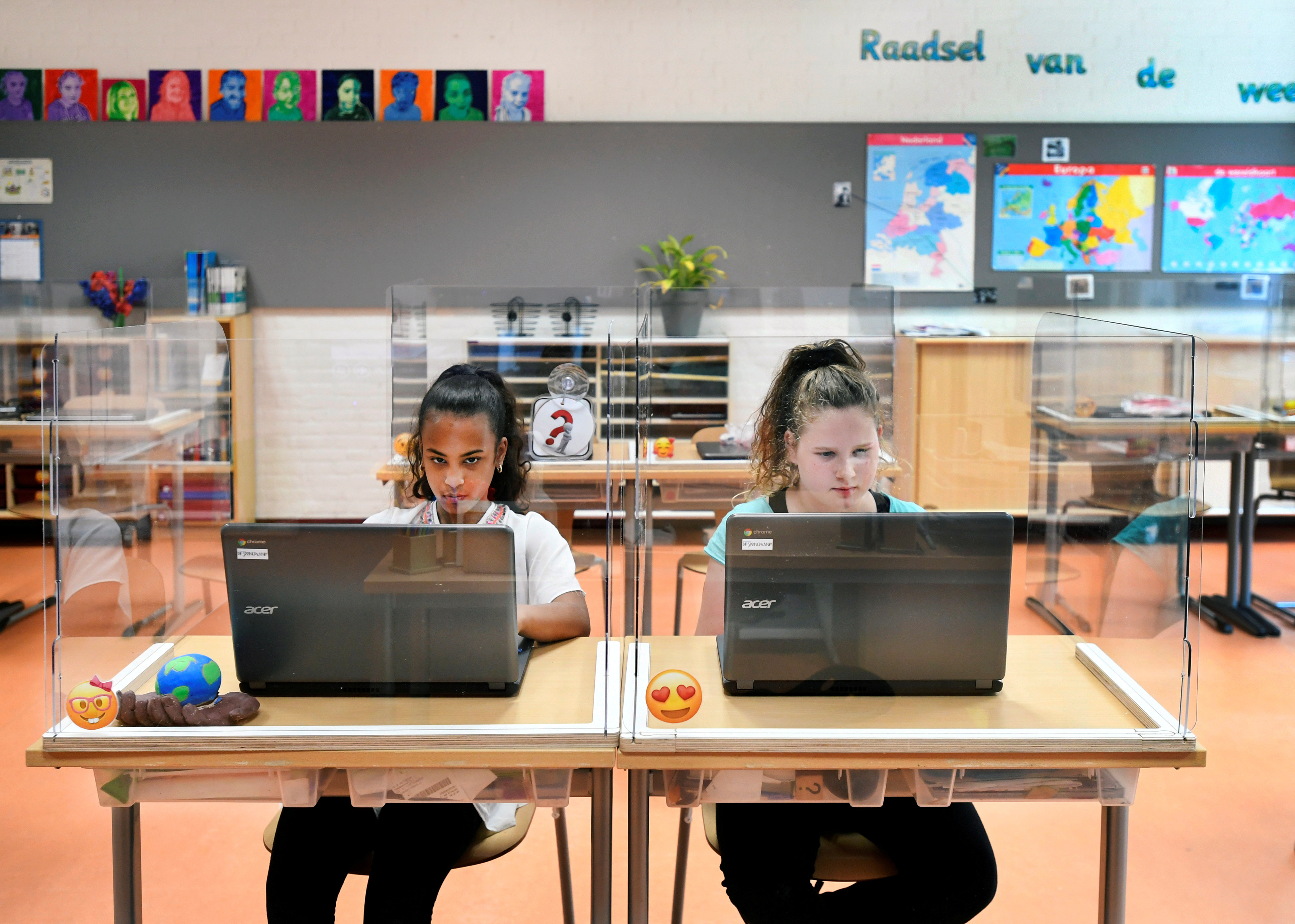 Pupils sitting behind partition boards made of plexiglass attend a class at a primary school, during the coronavirus disease (COVID-19) outbreak, in Den Bosch, Netherlands, May 8, 2020. REUTERS/Piroschka van de Wouw     TPX IMAGES OF THE DAY - RC2DKG9C47E1