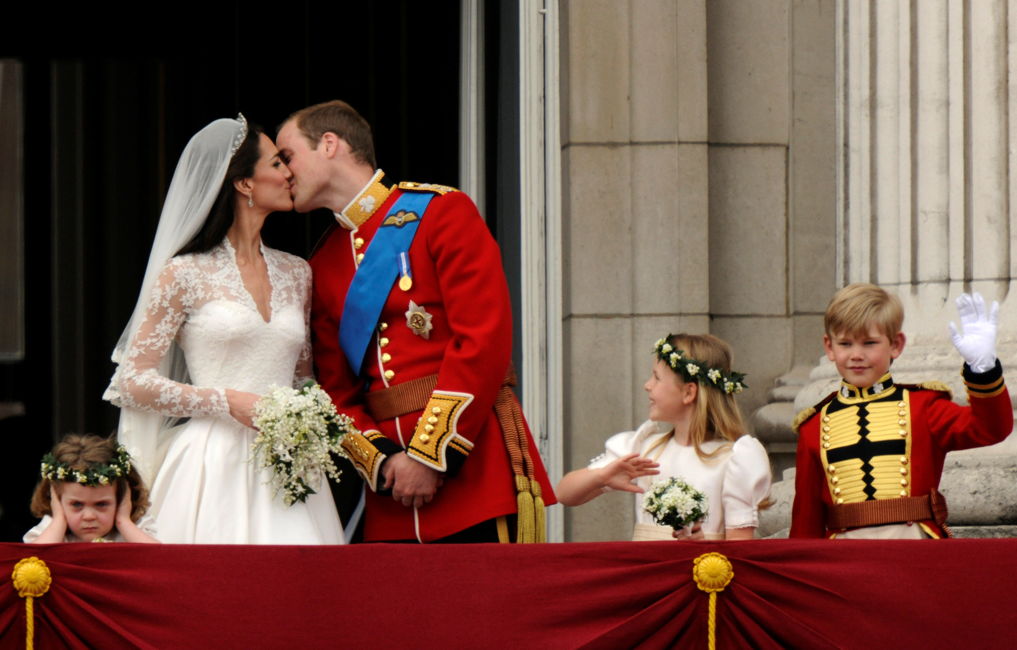 Britain's Prince William and his wife Catherine, Duchess of Cambridge, kiss on the balcony at Buckingham Palace, watched by bridemaids Grace van Cutsem (L), Margarita Armstrong-Jones and pageboy Tom Pettifer, after their wedding in Westminster Abbey in London, Britain, April 29, 2011