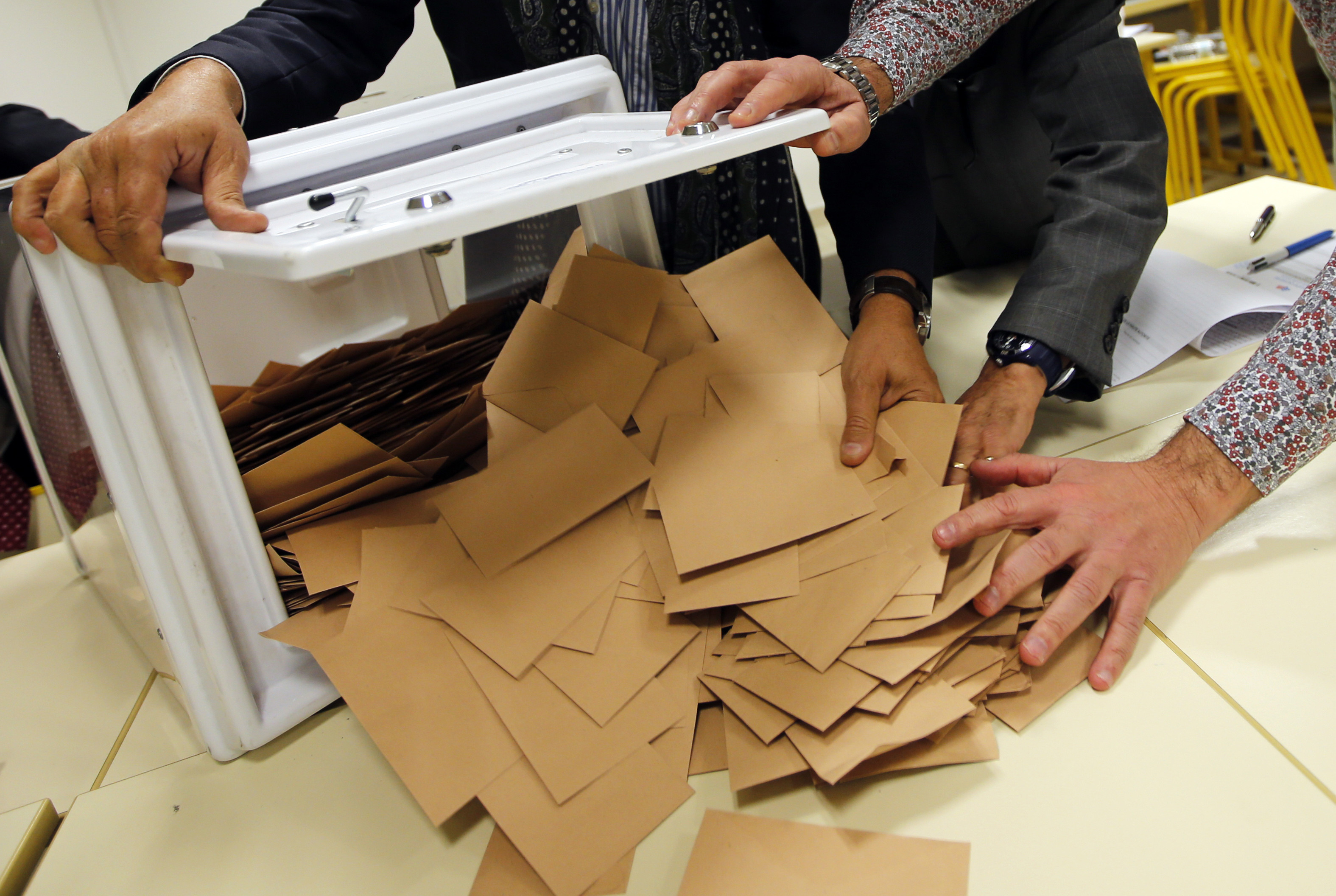 Officials gather ballots in the second round vote of the French center-right presidential primary election at a polling station in Marseille, France, November 27, 2016.