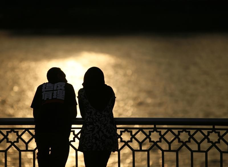 A couple watch a sunset near a lake in Putrajaya December 22, 2008.