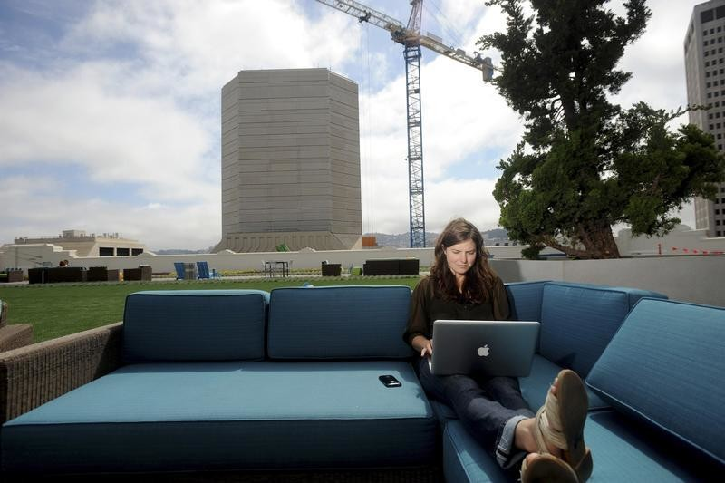 Jenna Sampson, a community relations manager at Twitter, works on the company's rooftop deck in San Francisco, California July 25, 2012.  The Olympics have presented a prime opportunity for Twitter to position itself as a new media channel that complements TV broadcasts - and carries the big-name ads to match.   REUTERS/Noah Berger (UNITED STATES - Tags: BUSINESS) - TM3E87Q0Q9V02