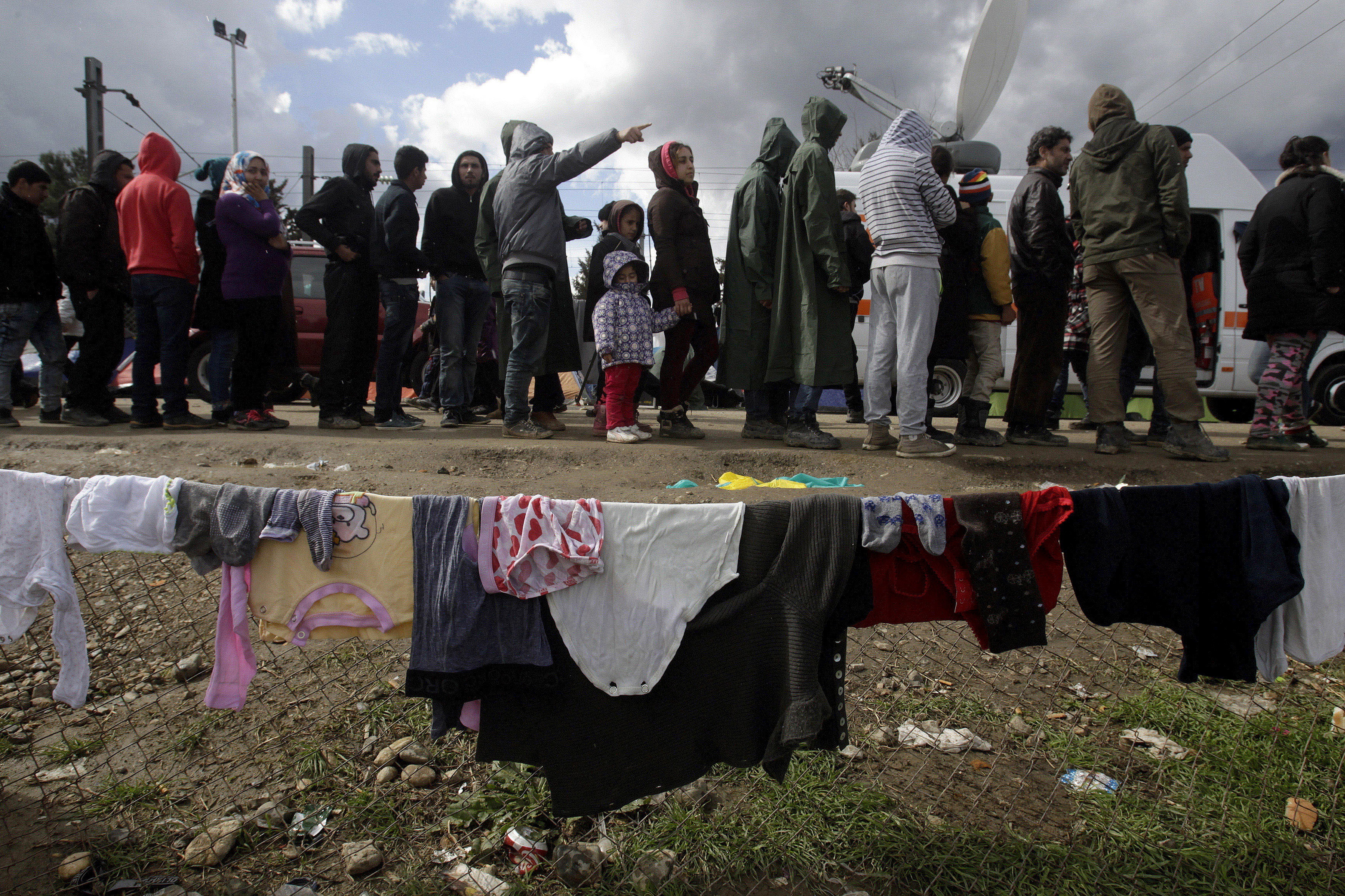 Refugees and migrants line up to receive aid in a makeshift camp at the Greek-Macedonian border, near the Greek village of Idomeni March 4, 2016.