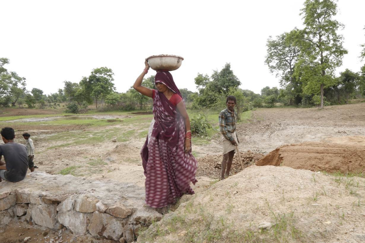 A Jal Saheli, or woman water friend, balances a container full of gravel to construct a new check dam in Agroutha village of Bundelkhand, India on July 16, 2019.