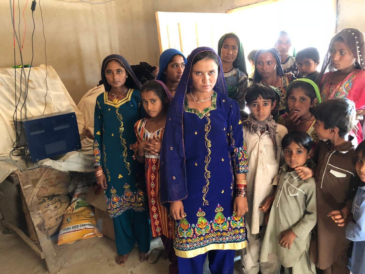 Women and children of the village of the village of Murid Khoso in Sindh province's Sujawal district, Pakistan, pose beside their prized possession -- battery hub with in-built charge controller