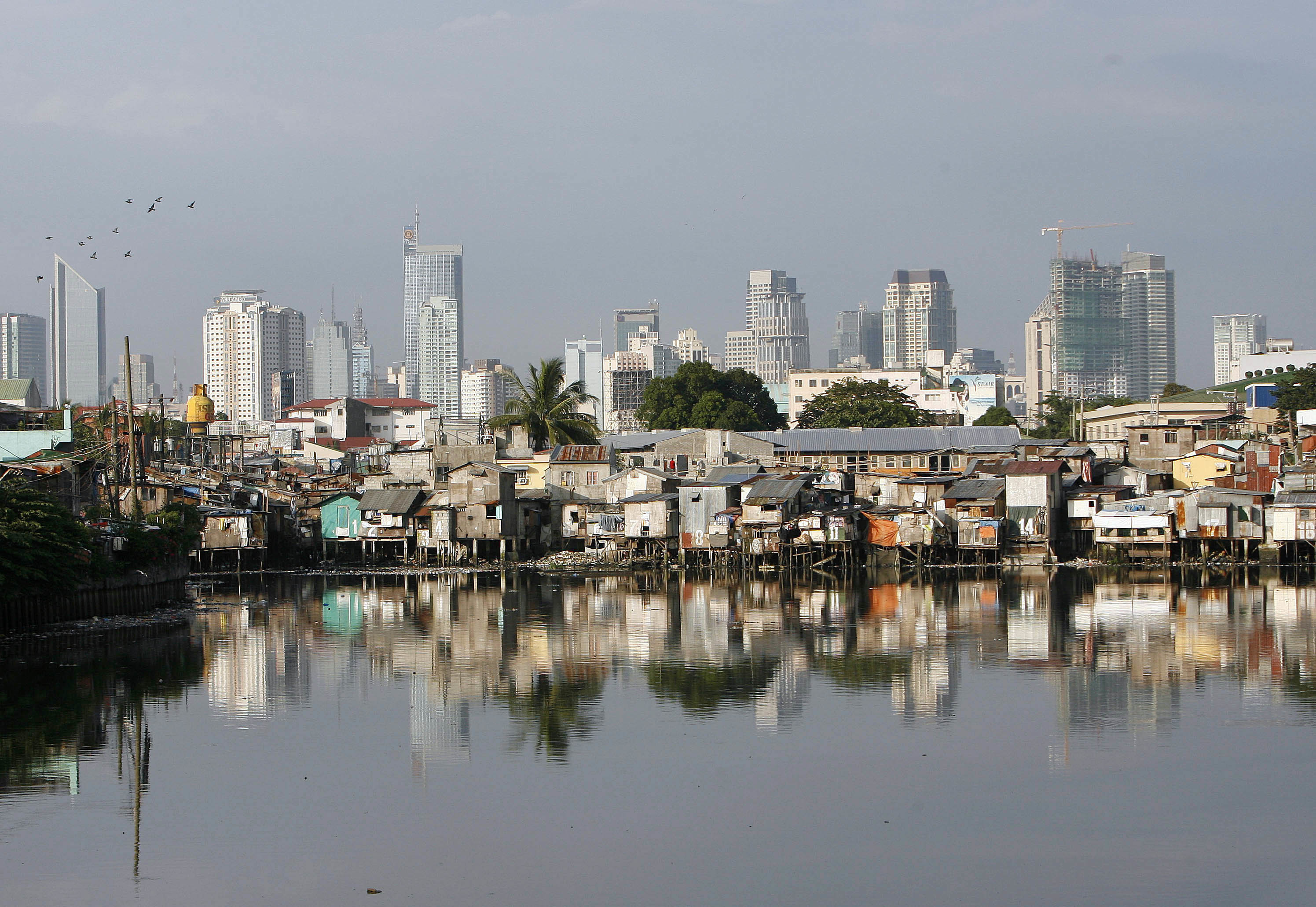 Slums are seen along a river with the skyline of Makati, Manila's financial district, in the background October 8, 2007. Developing countries in Asia are struggling to meet the UN-set millennium goals although the region is on course to cut extreme poverty, a report released on Monday showed.