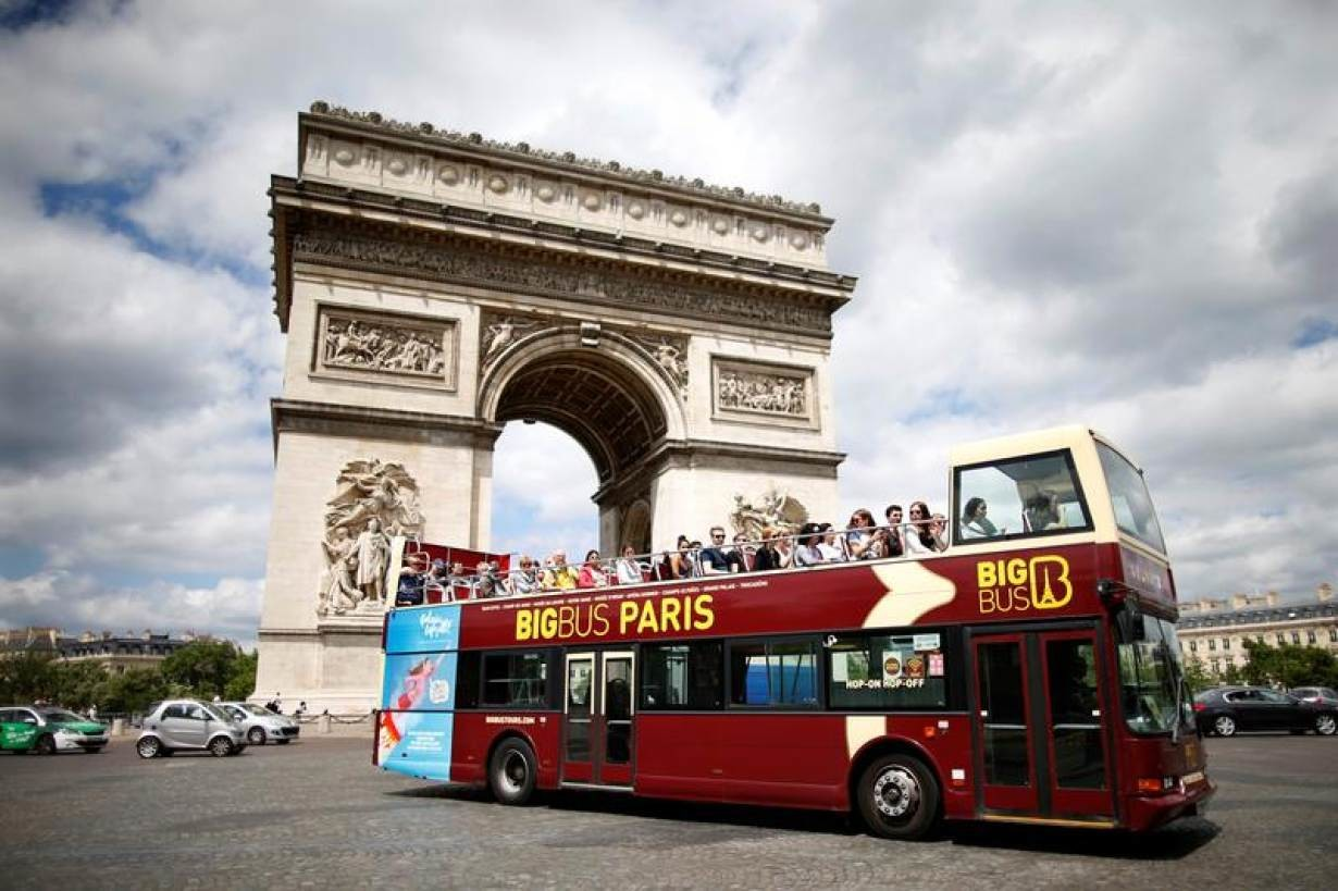 Tourists ride in an open-air double-decker bus past the Arc de Triomphe in Paris, France, May 30, 2017.