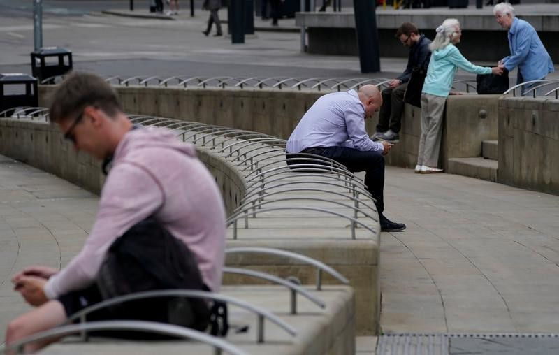 Men check their mobile phone as two women talk in Manchester, Britain July 7, 2017.