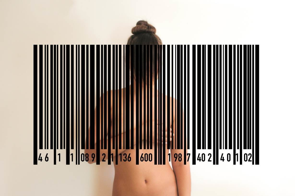 A woman is seen covering her breasts with one hand, with a barcode obscuring the upper half of her body.